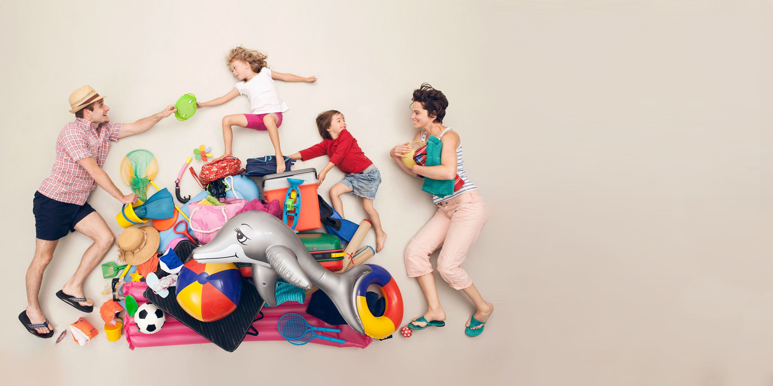 A father in a summer straw hat hands his young daughter a green plastic beach toy. She is on top of a pile of summer beach toys like a blow-up dolphin, a pool raft, shovels, a cooler...etc. Climbing on the pile is a younger boy wearing a red colored rash