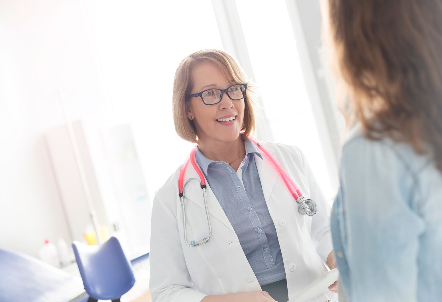 A doctor with a pink stethoscope and black glasses talks to her patient about her results