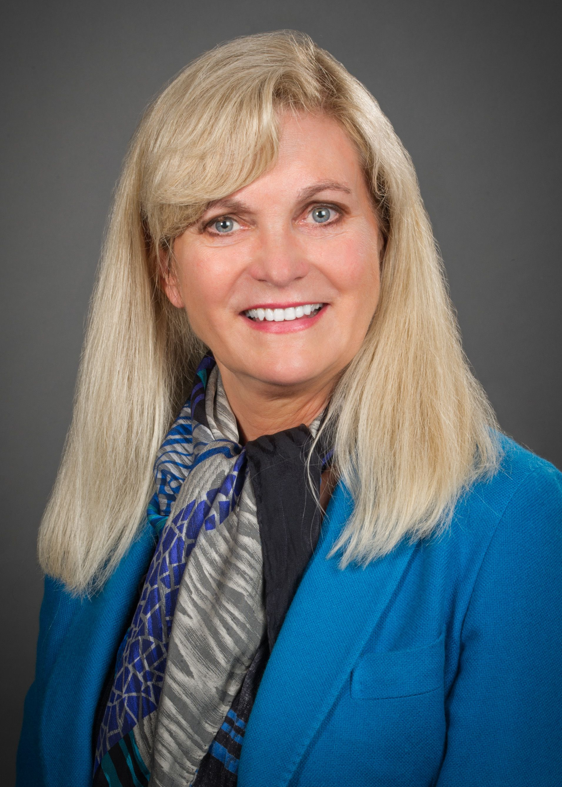 Cindy Grines, MD, wearing a blue jacket and multi-colored scarf