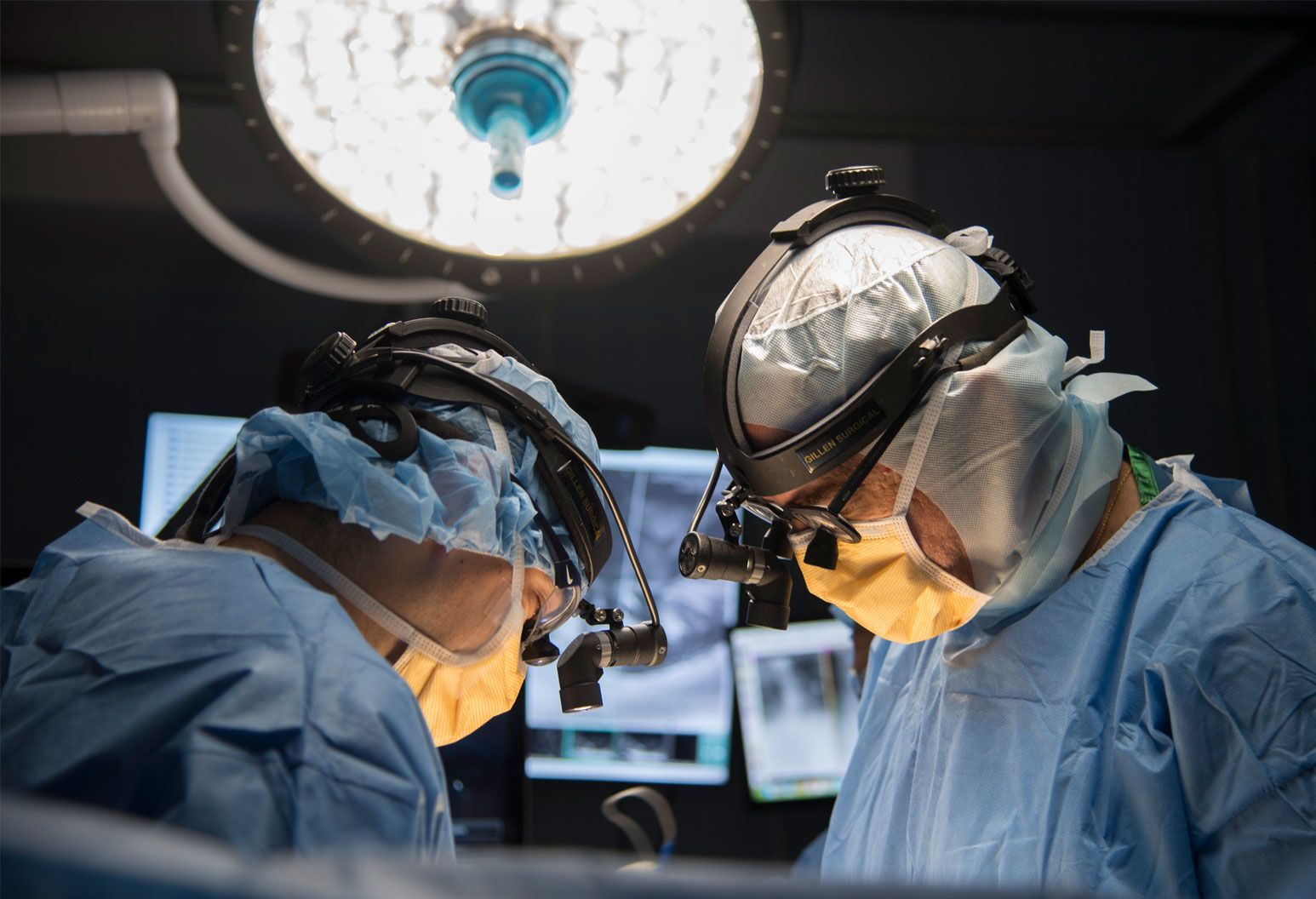 Two surgeons wearing scrubs, masks and eye magnifying glasses perform surgery.