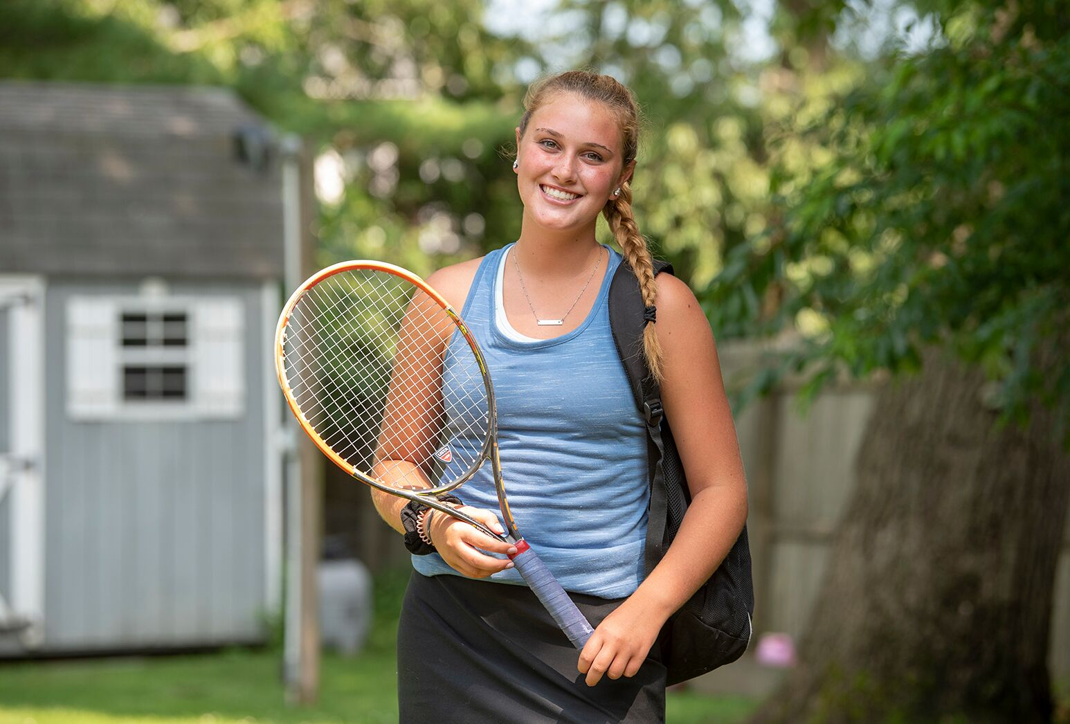 Teenage girl with a long blonde braid in a blue sleeveless top, holding a tennis racket.
