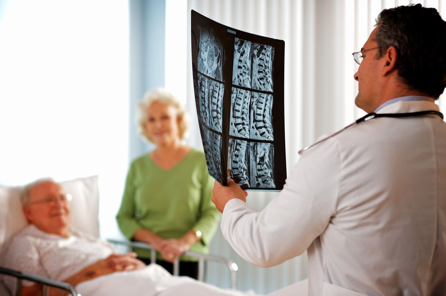 A doctor reviews diagnostic imaging of an elderly man's spine.