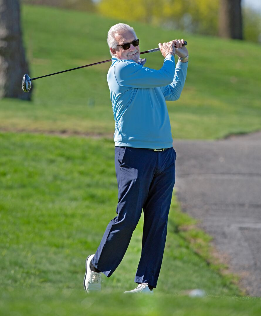 Hockey Hall of Famer Clark Gillies swinging a golf club at a golf course.