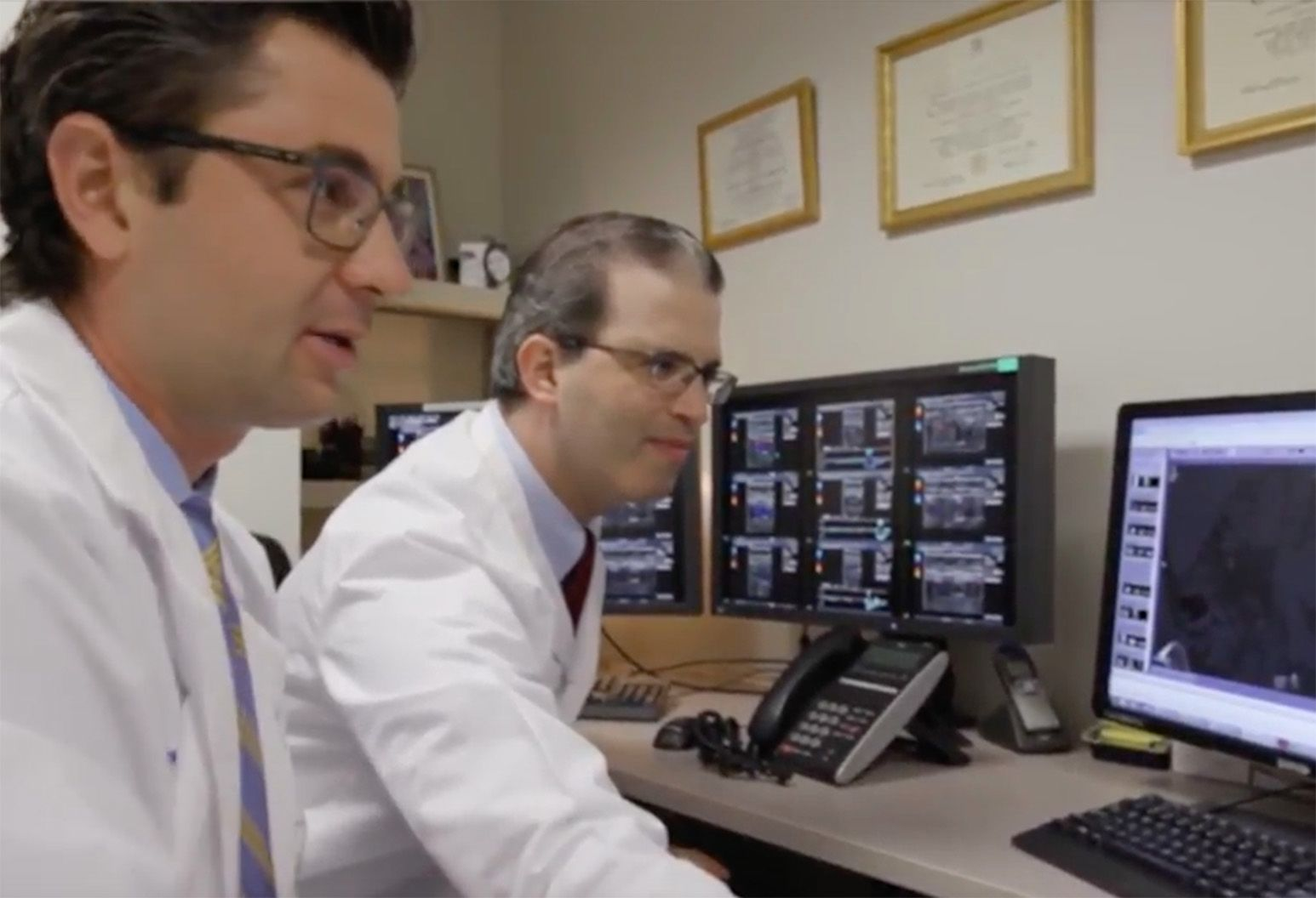 Two male doctors in white coats and glasses observe a computer screen.