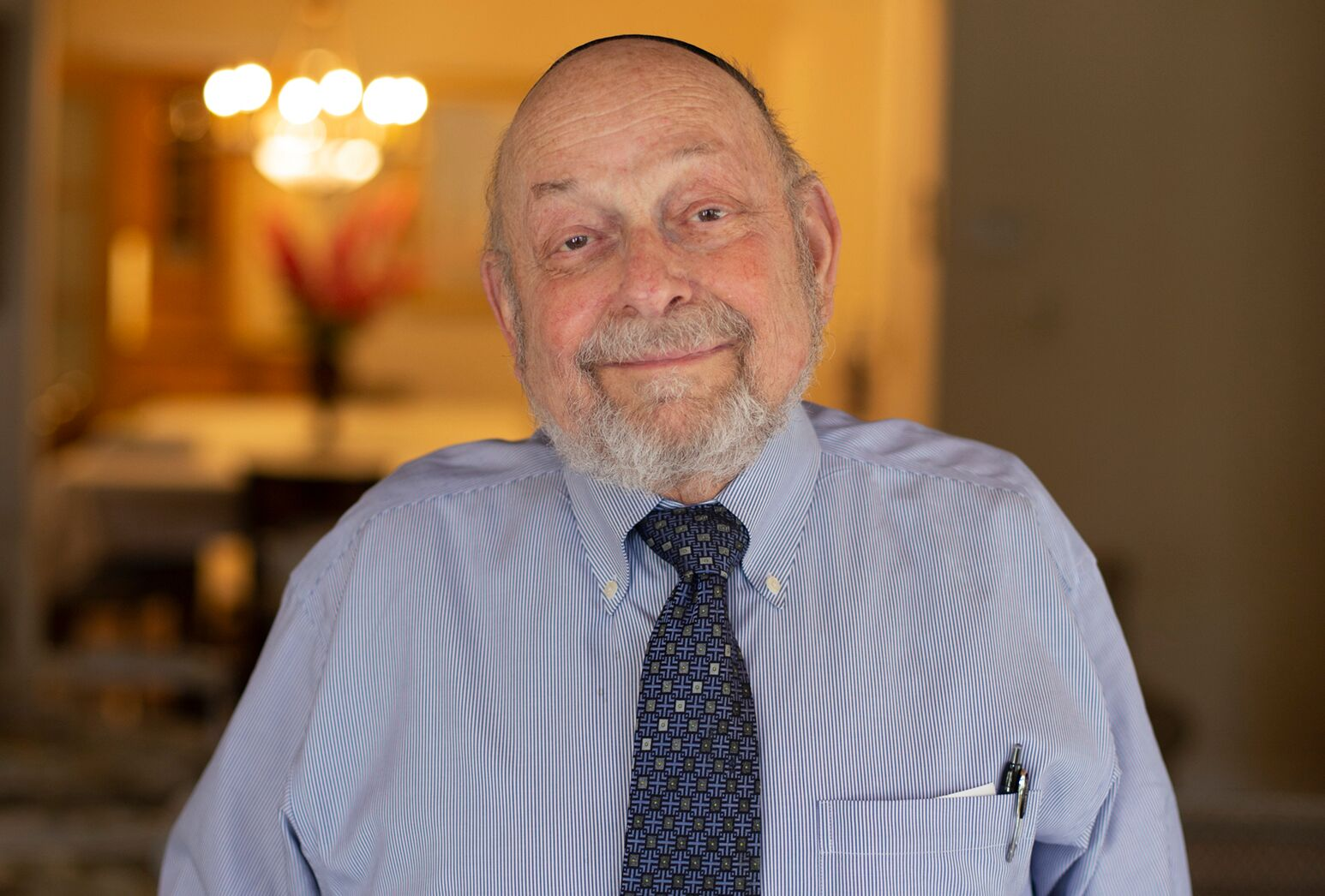 Older man wearing a blue collared shirt and tie smiles in his home.
