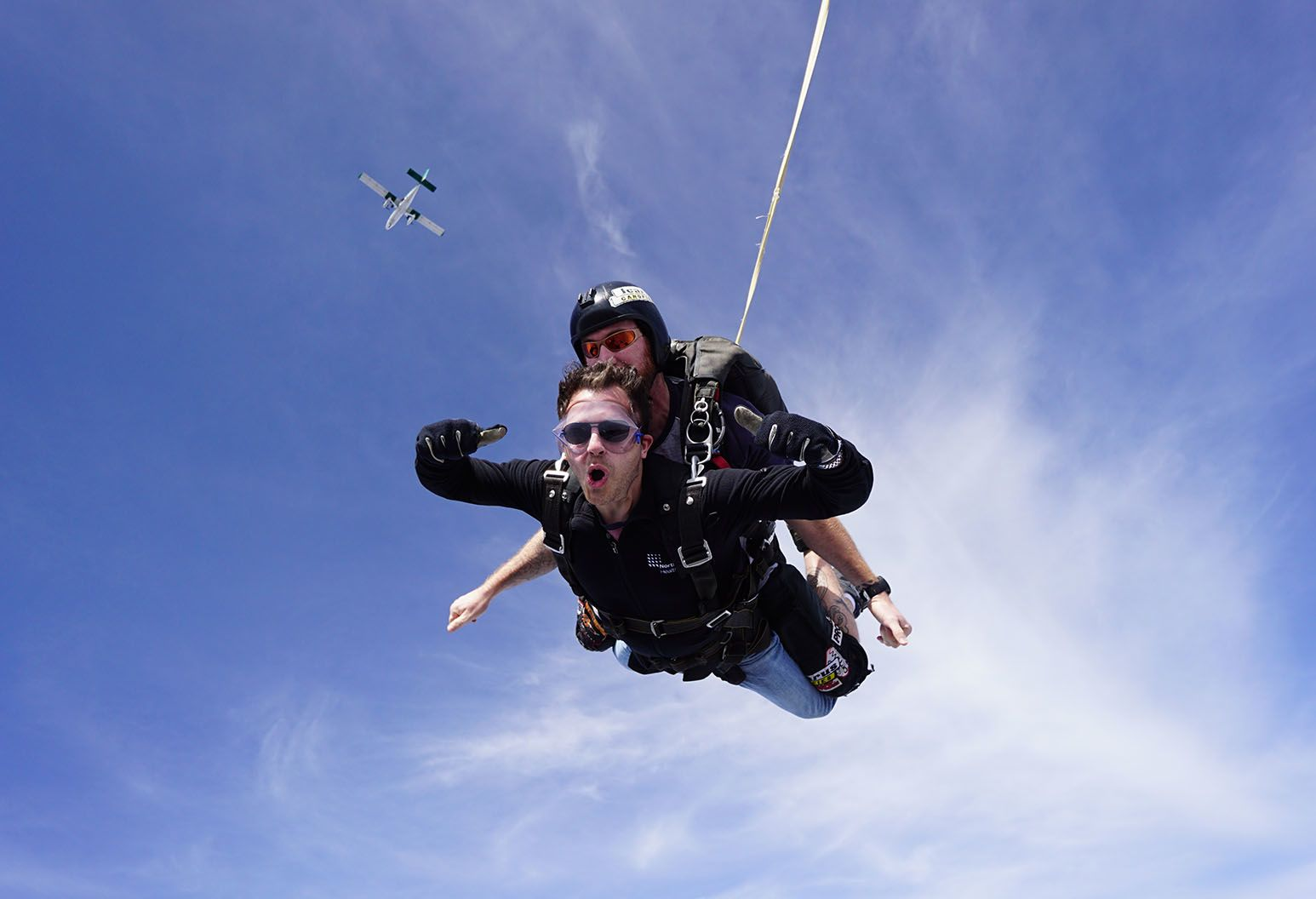 Man sky diving, giving camera two thumbs up