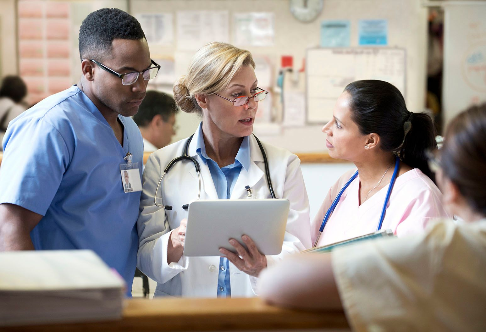 Three doctors discuss an emergent situation. One of them is speaking and pointing her the electronic tablet she is holding.