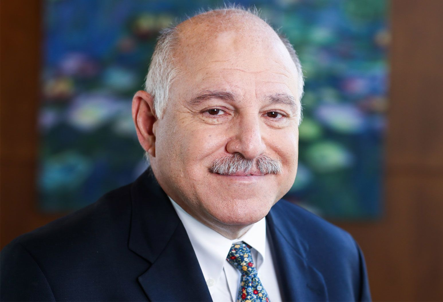 An elderly bald man, with white hairs on the side and a white mustache smiles at the camera wearing a suit with a multicolored tie.
