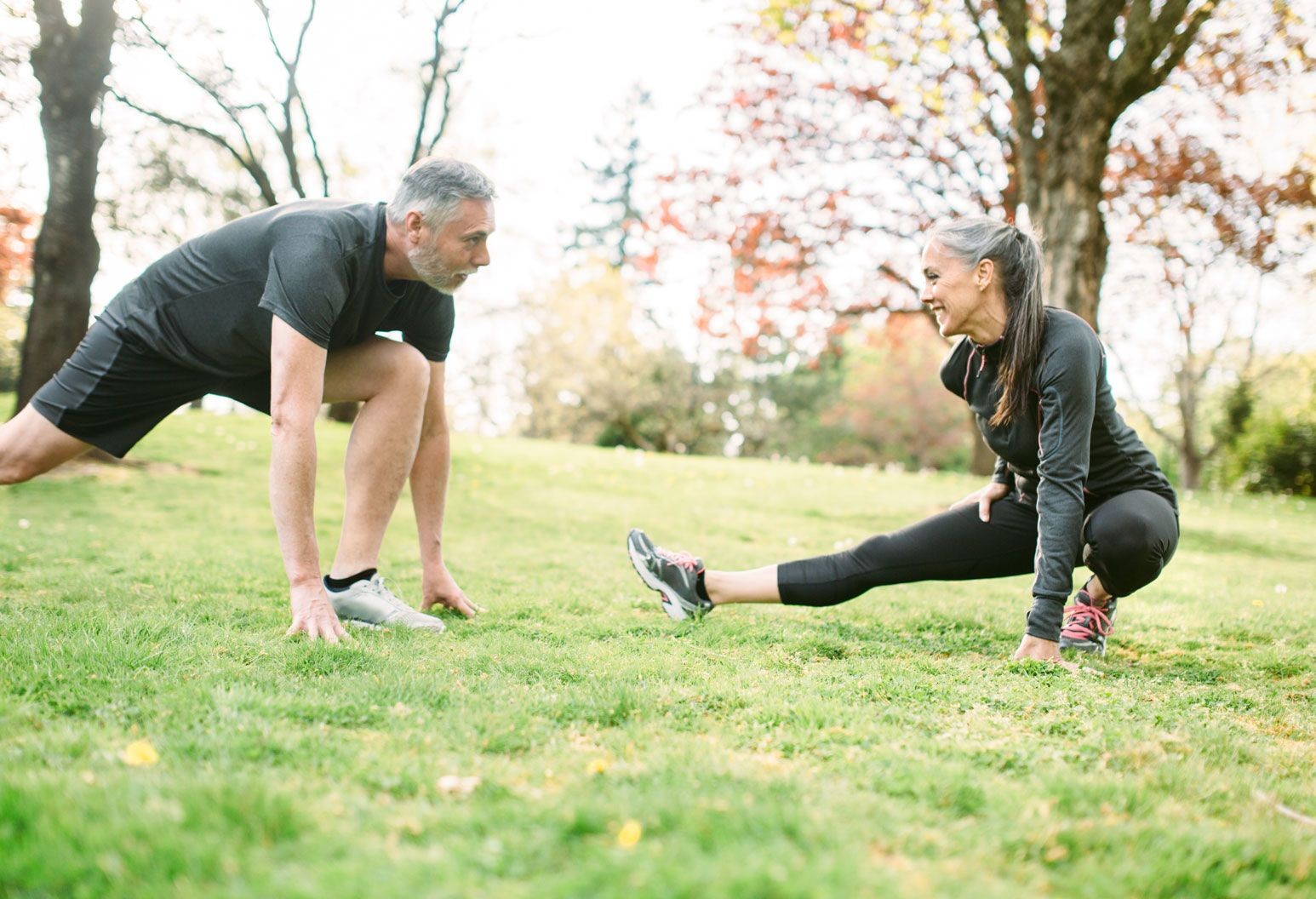An elderly man and woman stretch outside on the grass during fall. They are both wearing black and looking at each other.There are trees in the background.