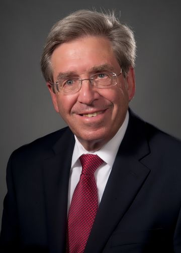 Alan Mensch, MD, wearing a red tie