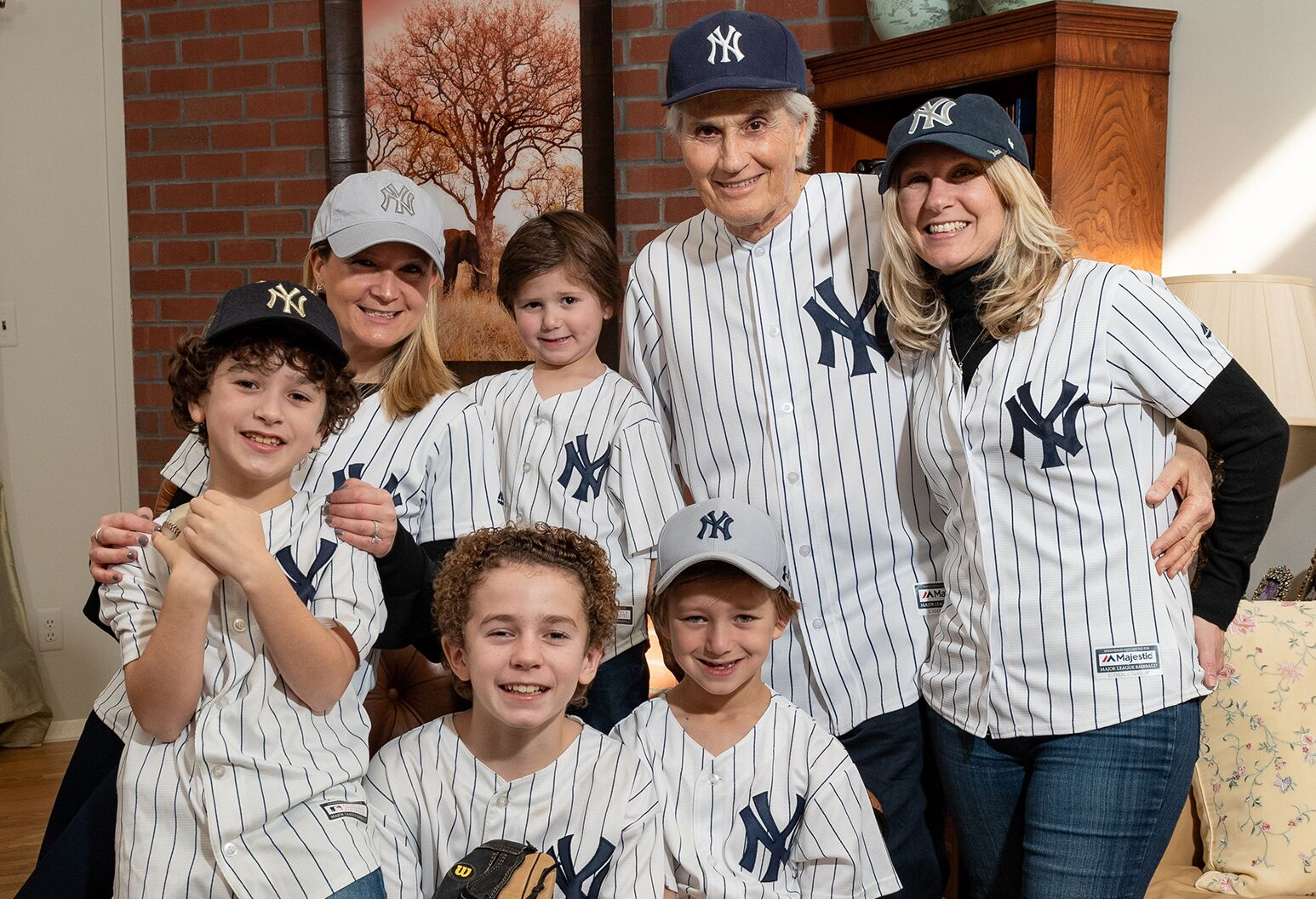 Three generations of a family smile and wear Yankees shirts in a living room.