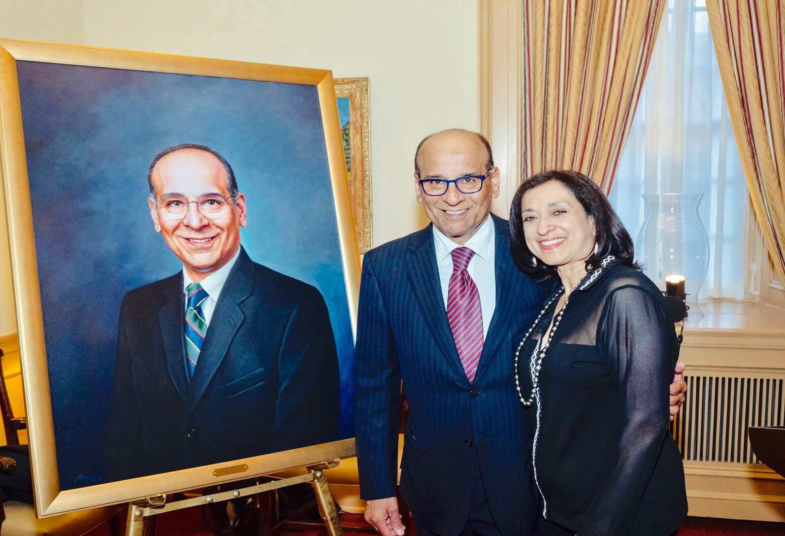 Raj Narayan, MD, and his wife, Tina, stand beside a painted portrait at the University of Cincinnati.