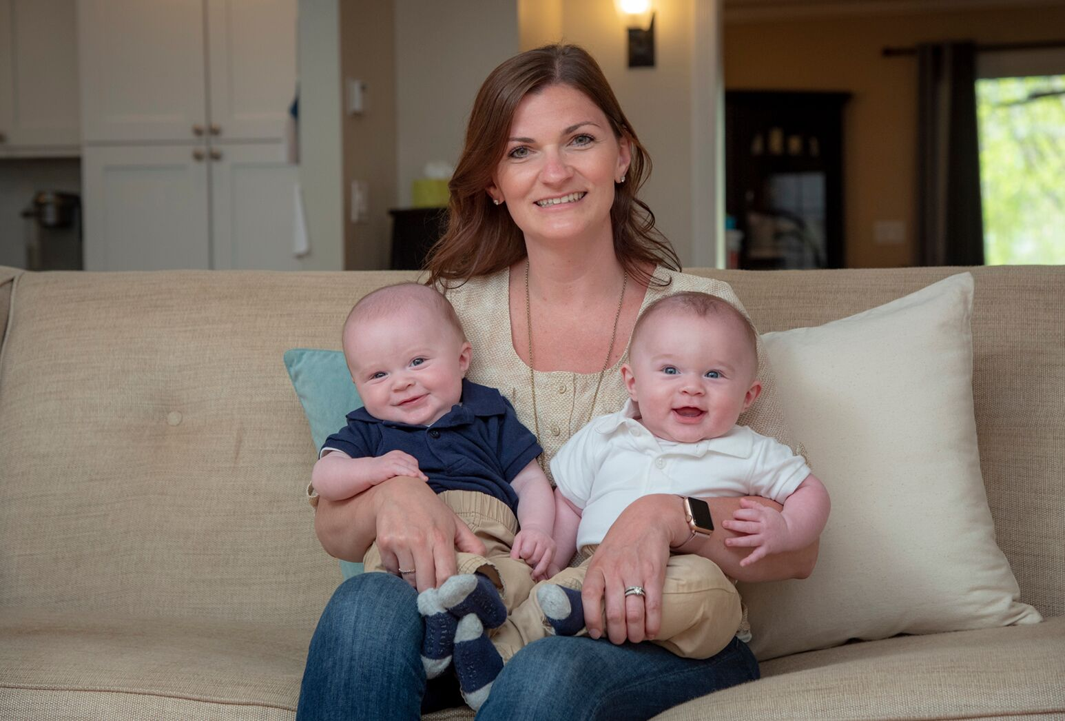 Mother sitting on a couch holding her twin baby boys.