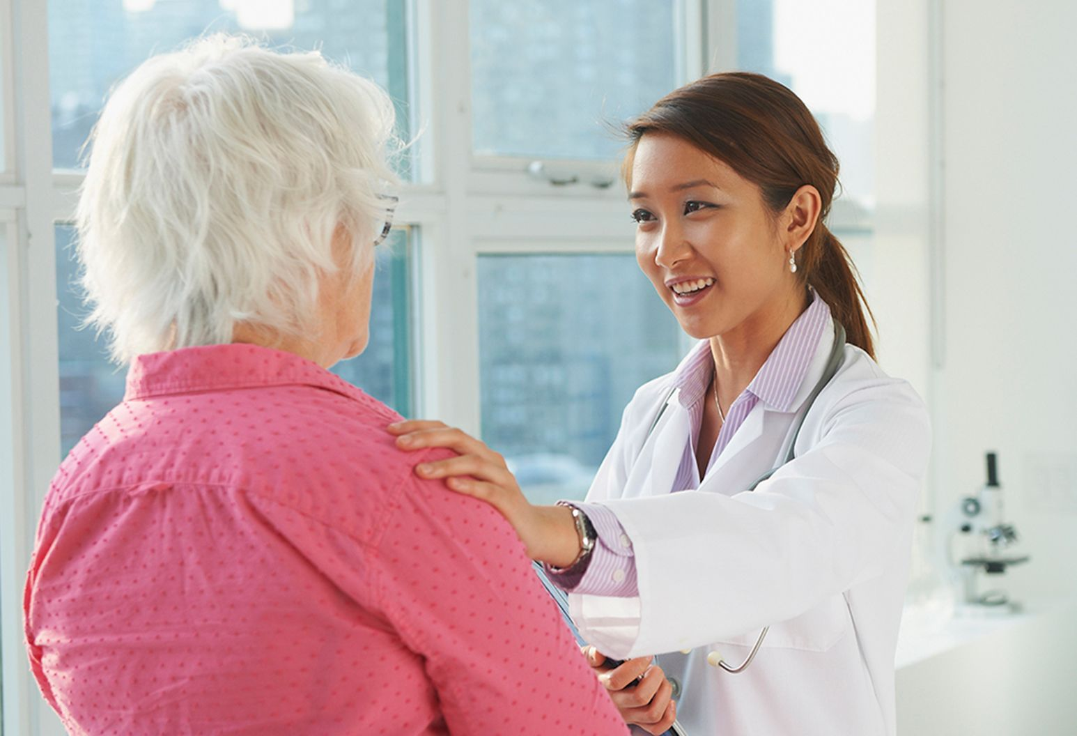 A cheerful female doctor smiles at an elderly female patient.