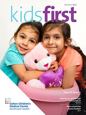 Cover of news brochure, two young girls hugging a teddy bear.