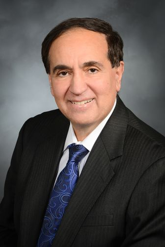 Frank Chervenak, MD, wearing a blue tie and striped suit