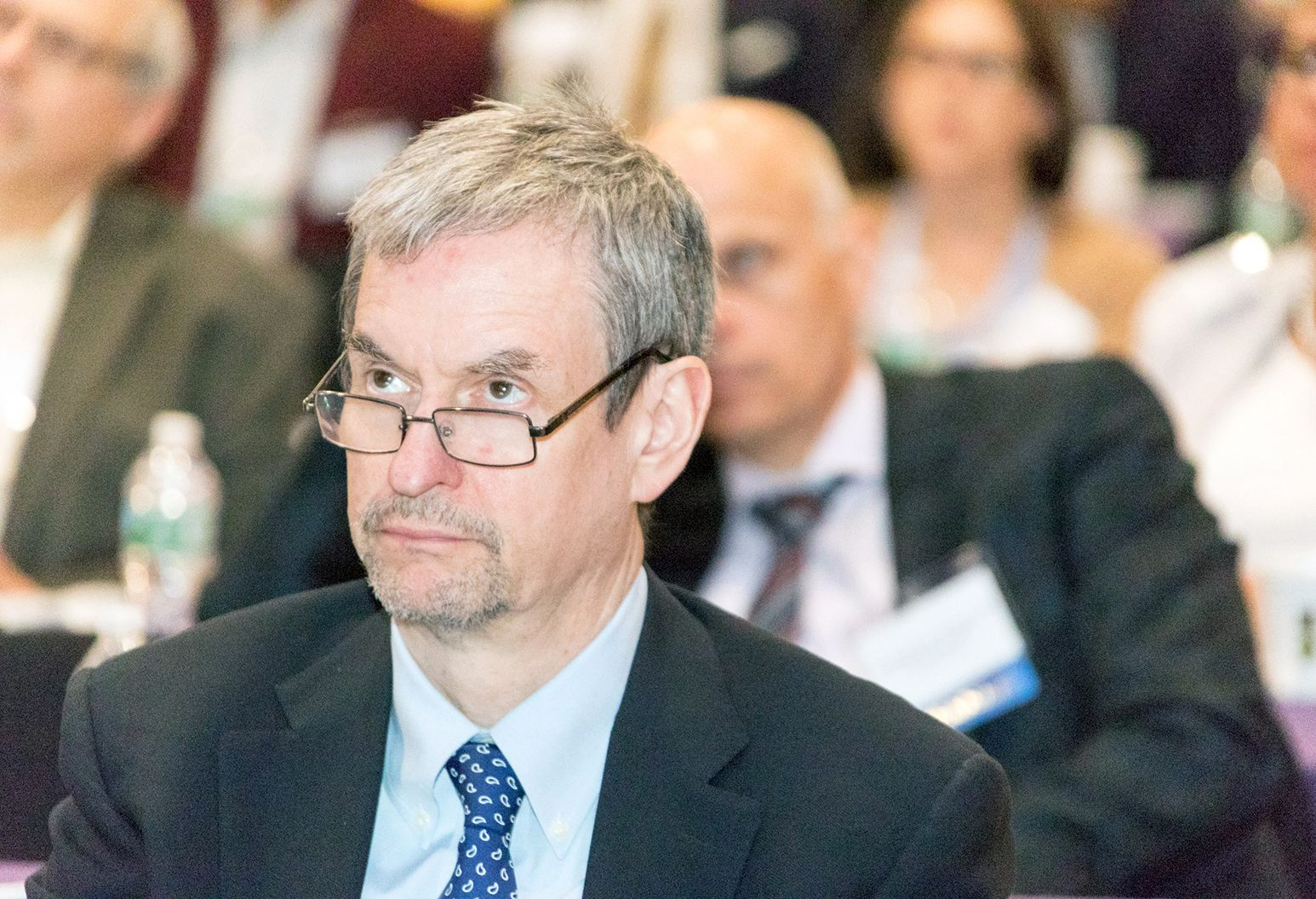 Middle aged man wearing a suit and glasses is watching a presentation at a conference