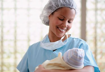 Female physician in blue scrubs, cradling and gazing down at new born baby