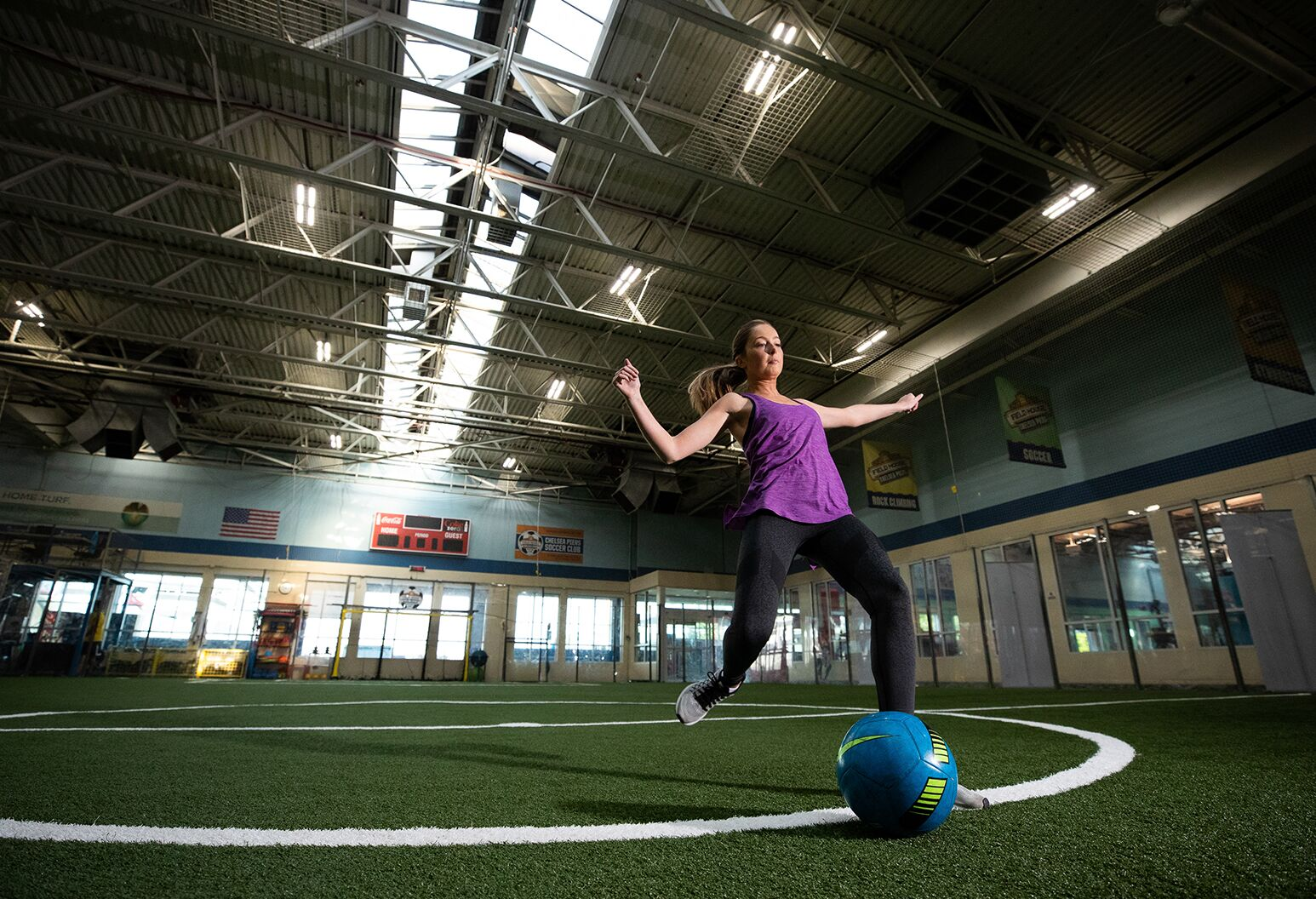 Young female athlete is kicking a ball on an indoor soccer field