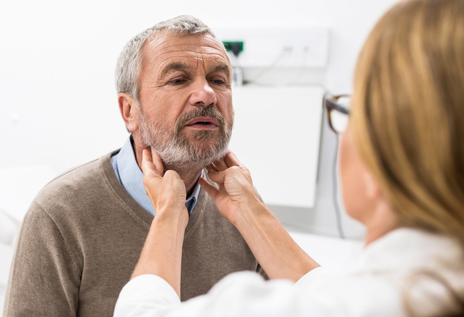 Older man getting his throat glad examined by a doctor