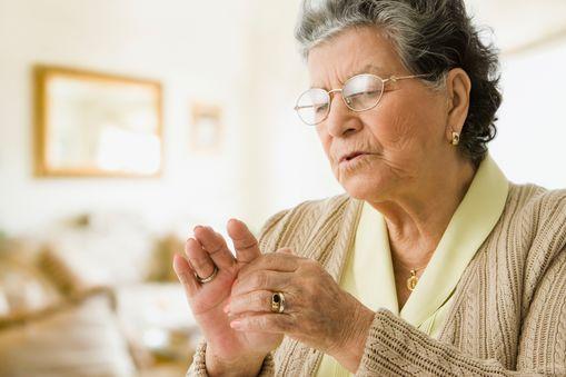 An elderly woman holds her hand