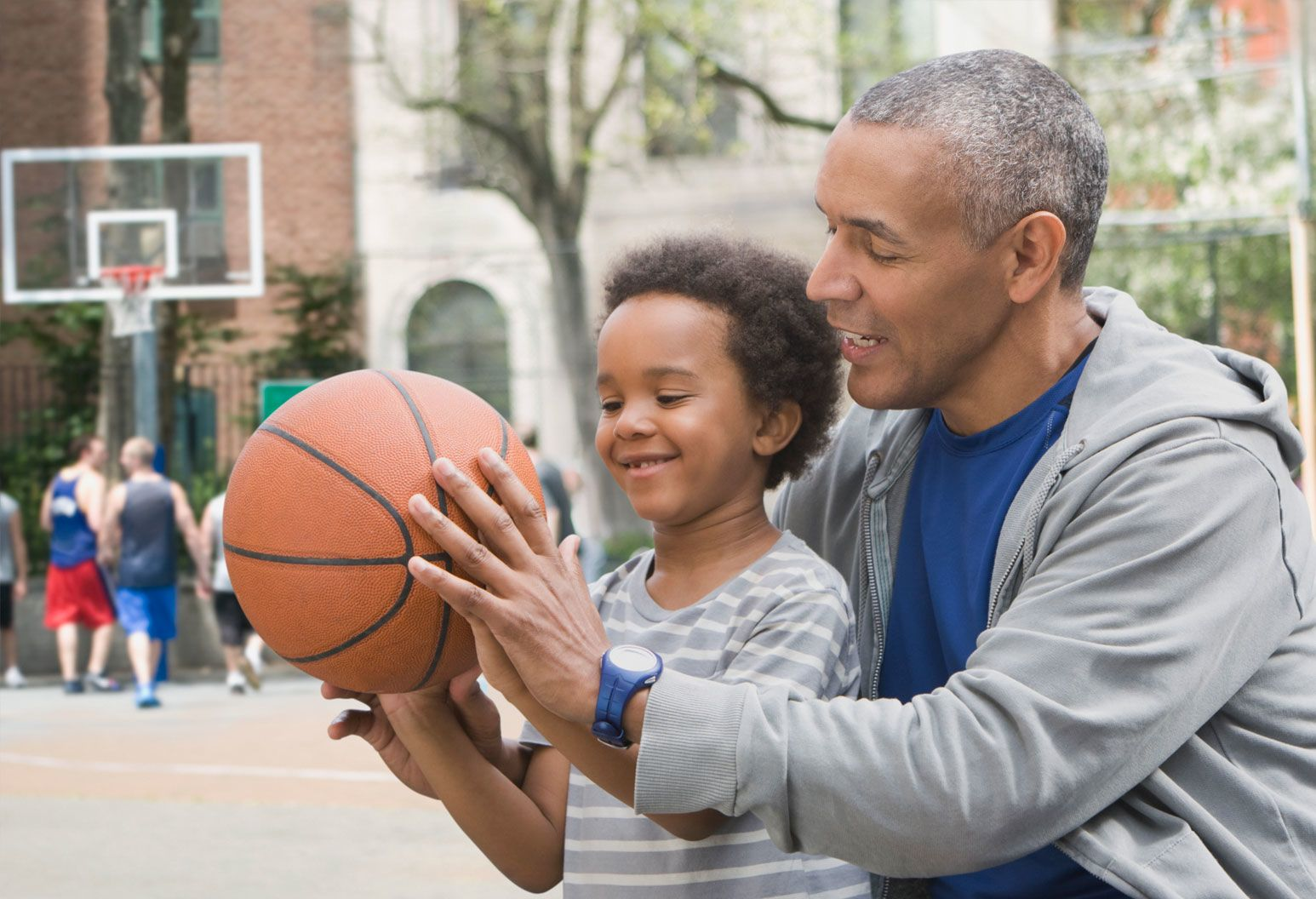 A middle-aged man and child are at a basketball court at the park, holding the ball together and smiling.