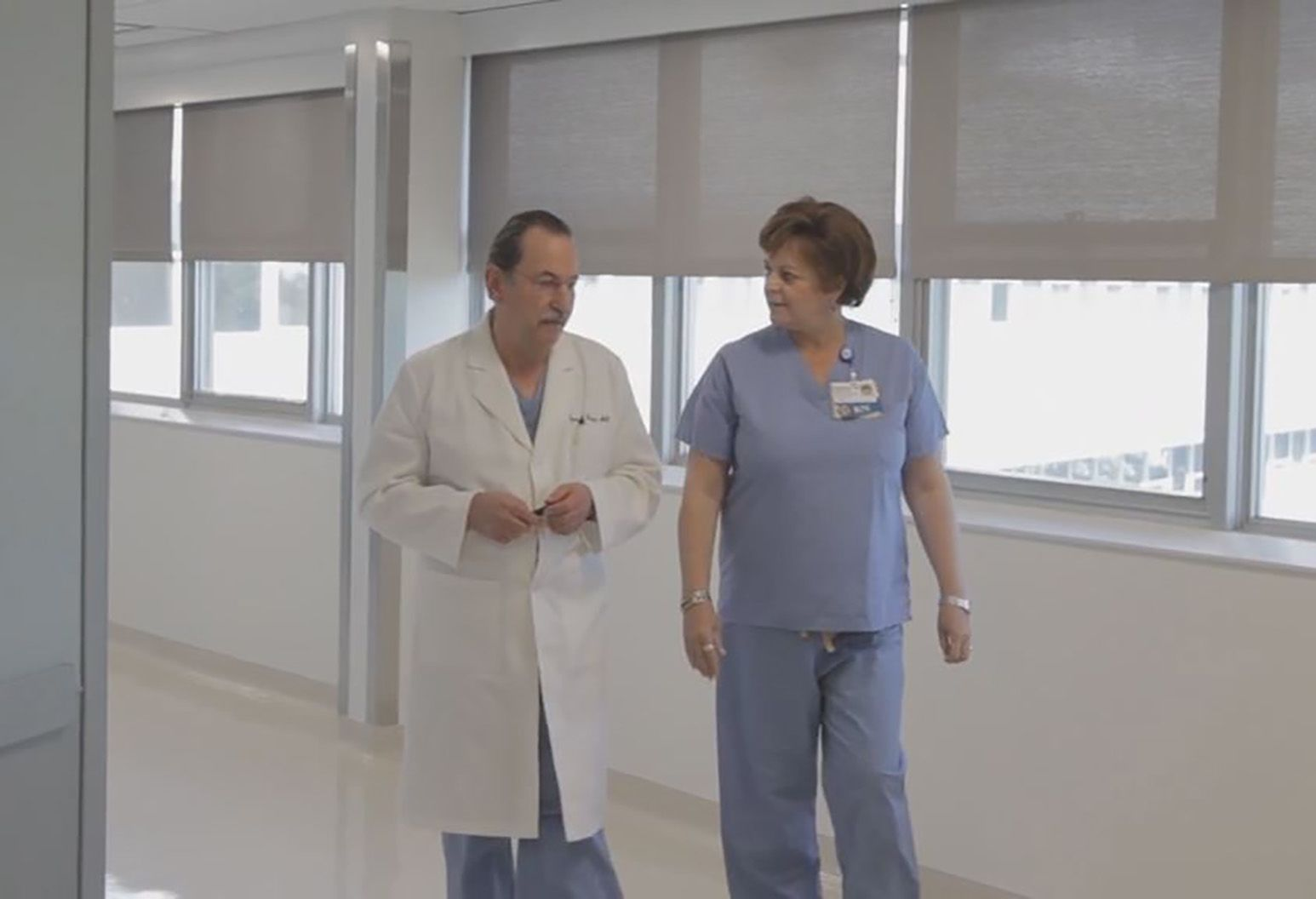 A male doctor and a female nurse walk in the hallway of a hospital. The doctor is wearing a white lab coat and is the nurse is wearing blue scrubs.