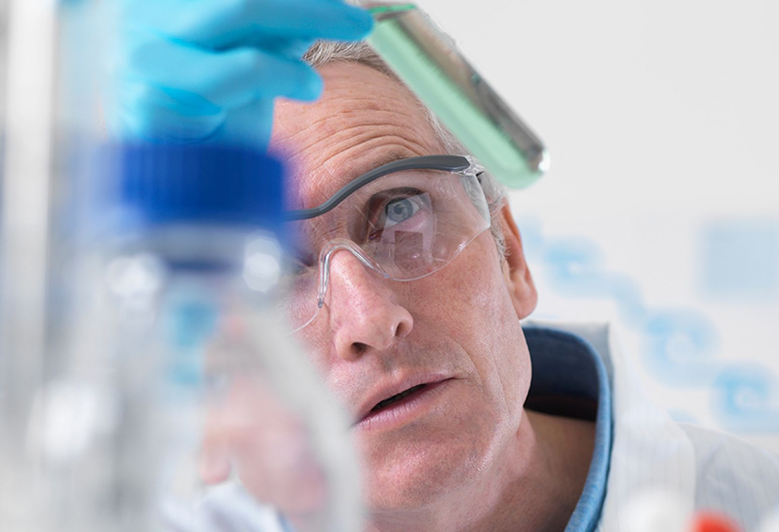 male researcher in safety glasses, examining a test tube