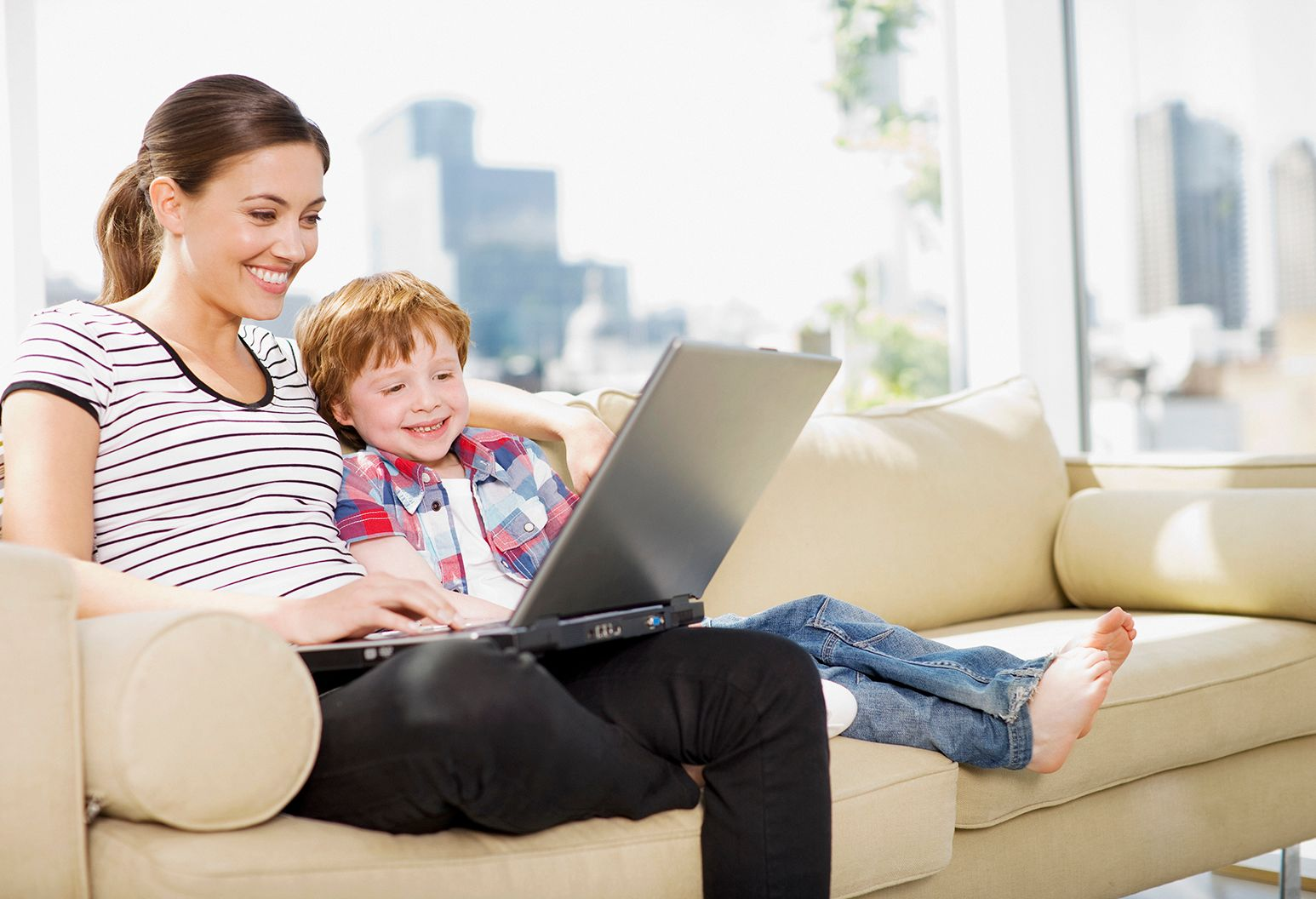 A mother and her young boy with red hair sit on a beige couch looking at a laptop computer. She is wearing a black and white striped shirt and he is wearing a red and blue flannel.