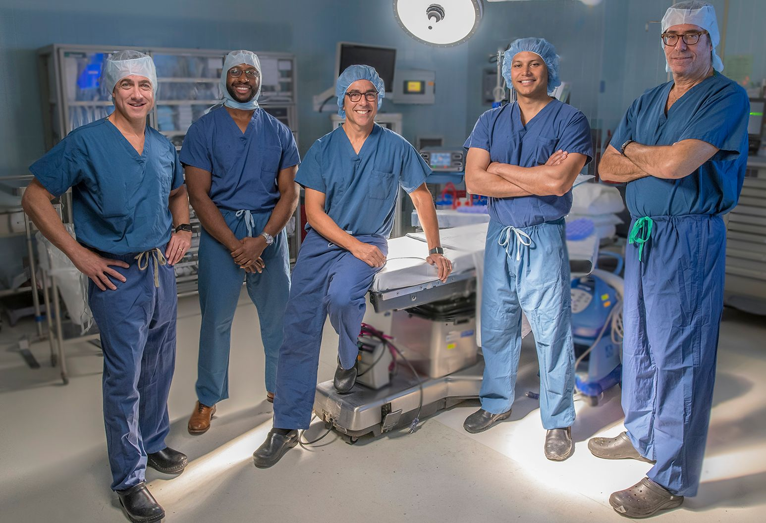 Group of surgeons wearing surgical scrubs pose for a group photograph in an operating roon