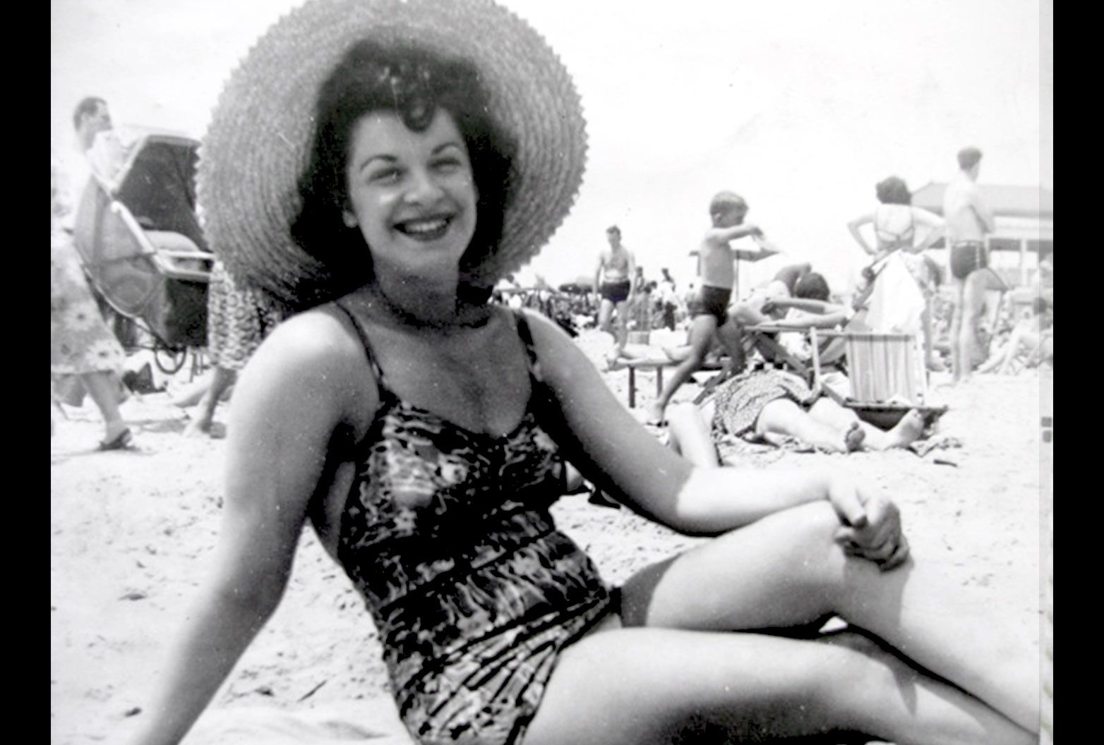 Black and white photo of a young woman sitting on the sand at a beach in a one piece bathing suit. She is wearing a large straw hat and smiling for the camera.