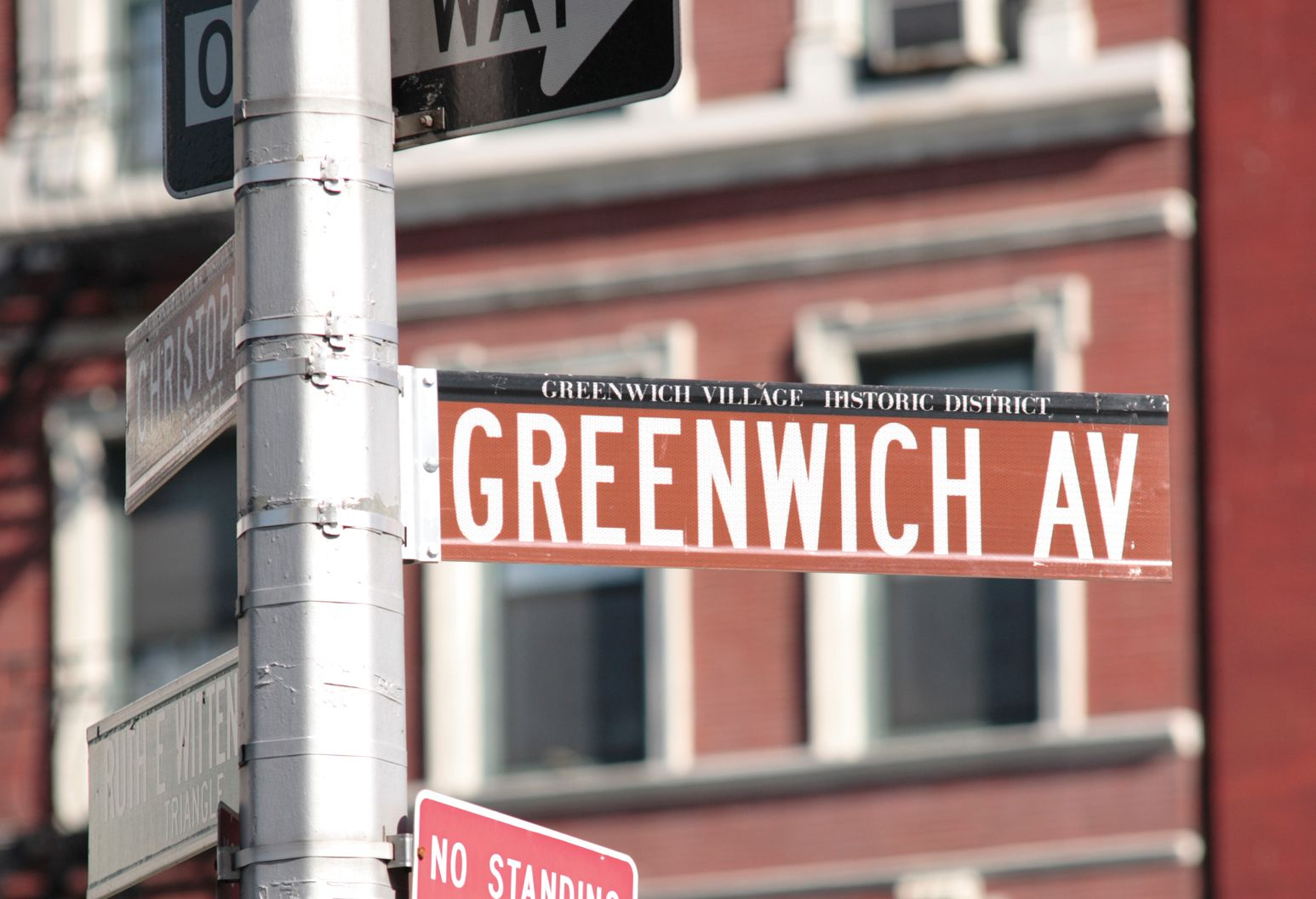 Auburn colored street sign of Greenwich Avenue, within the Greenwich Village Historic District