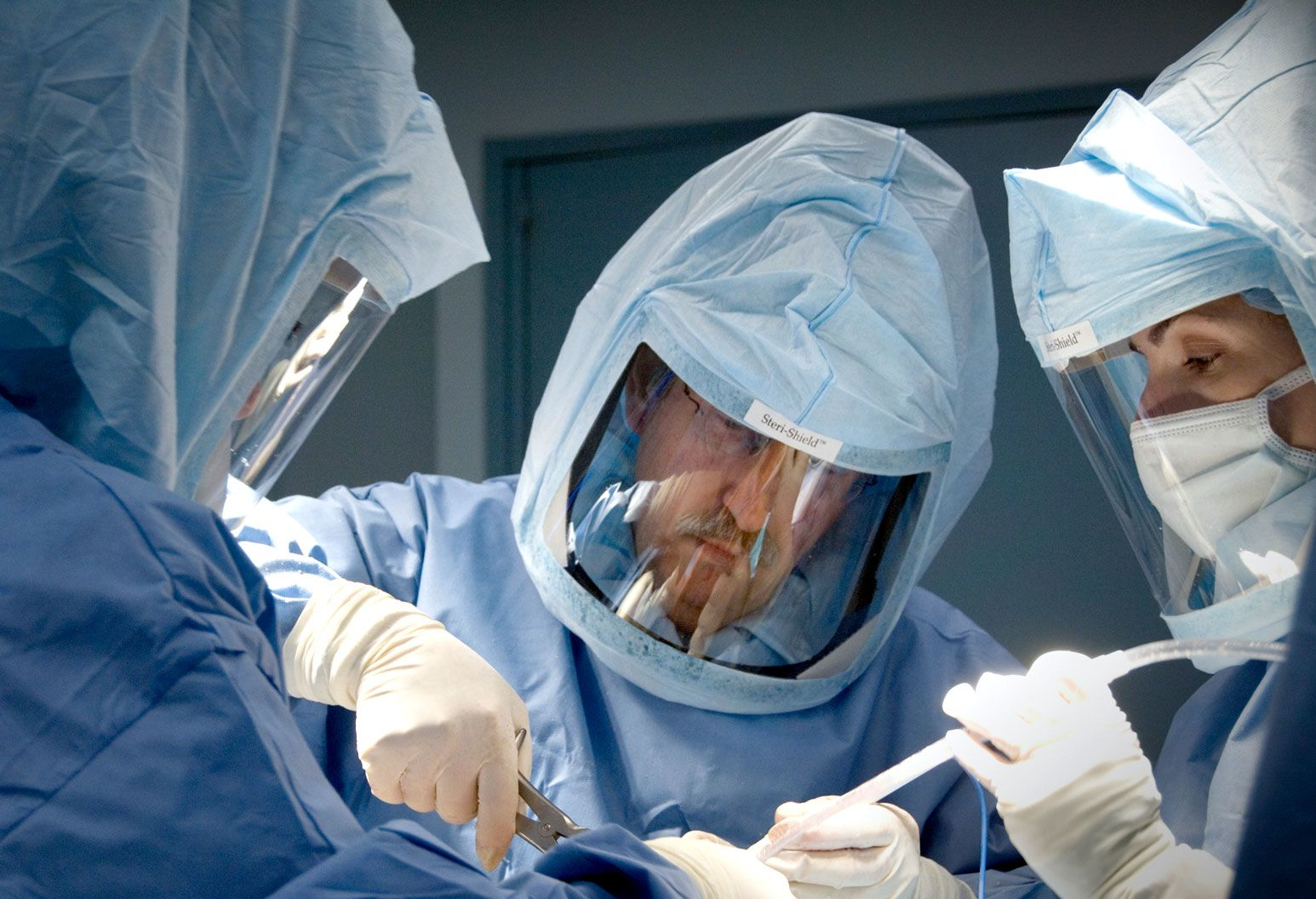 Three surgeons wearing scrubs and masks over their faces perform surgery. The focus is on the male doctor in the middle who is cutting a tube with surgical equipment.