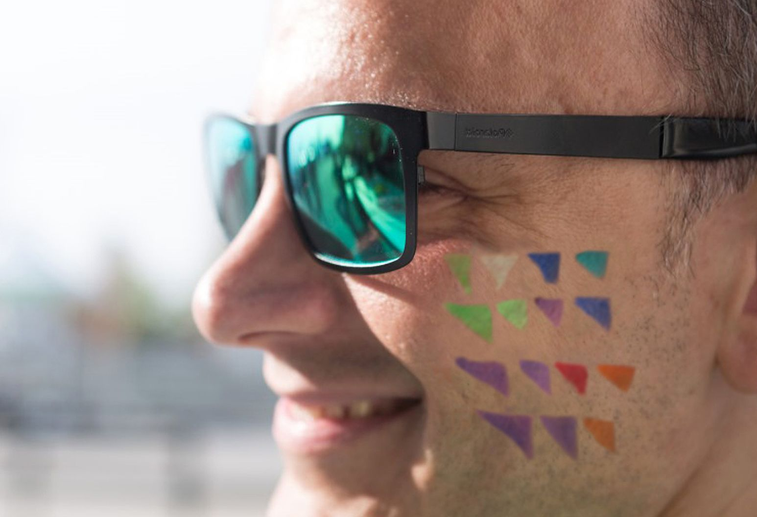 Man's face with sunglasses, Northwell logo painted on his cheek
