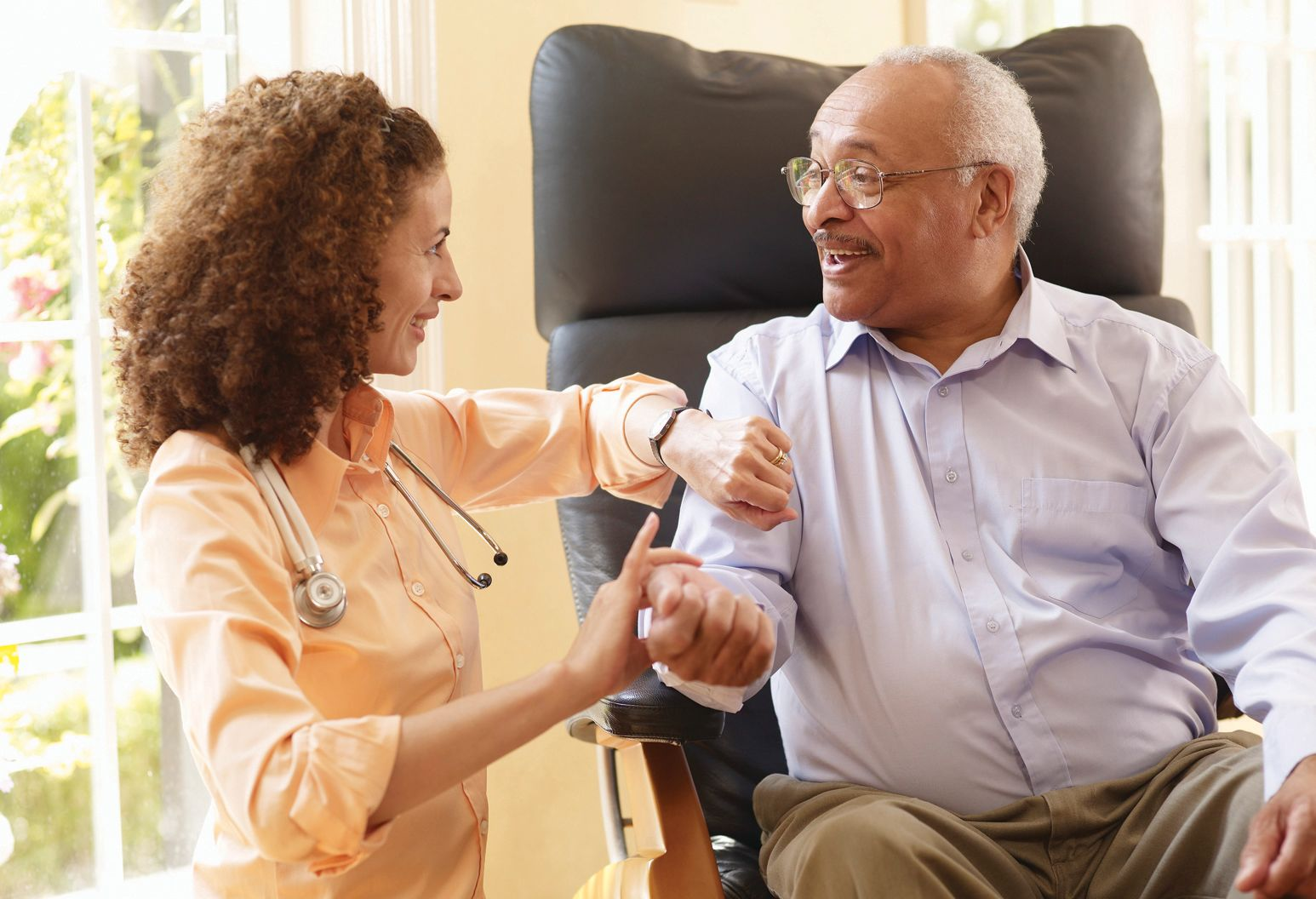 female physician smiling while checking pulse of elderly man sitting in chair