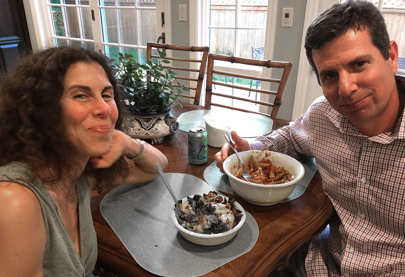 A man and woman smiles for the camera as they sit at a dining table with bowls of pasta and seafood in front of them.