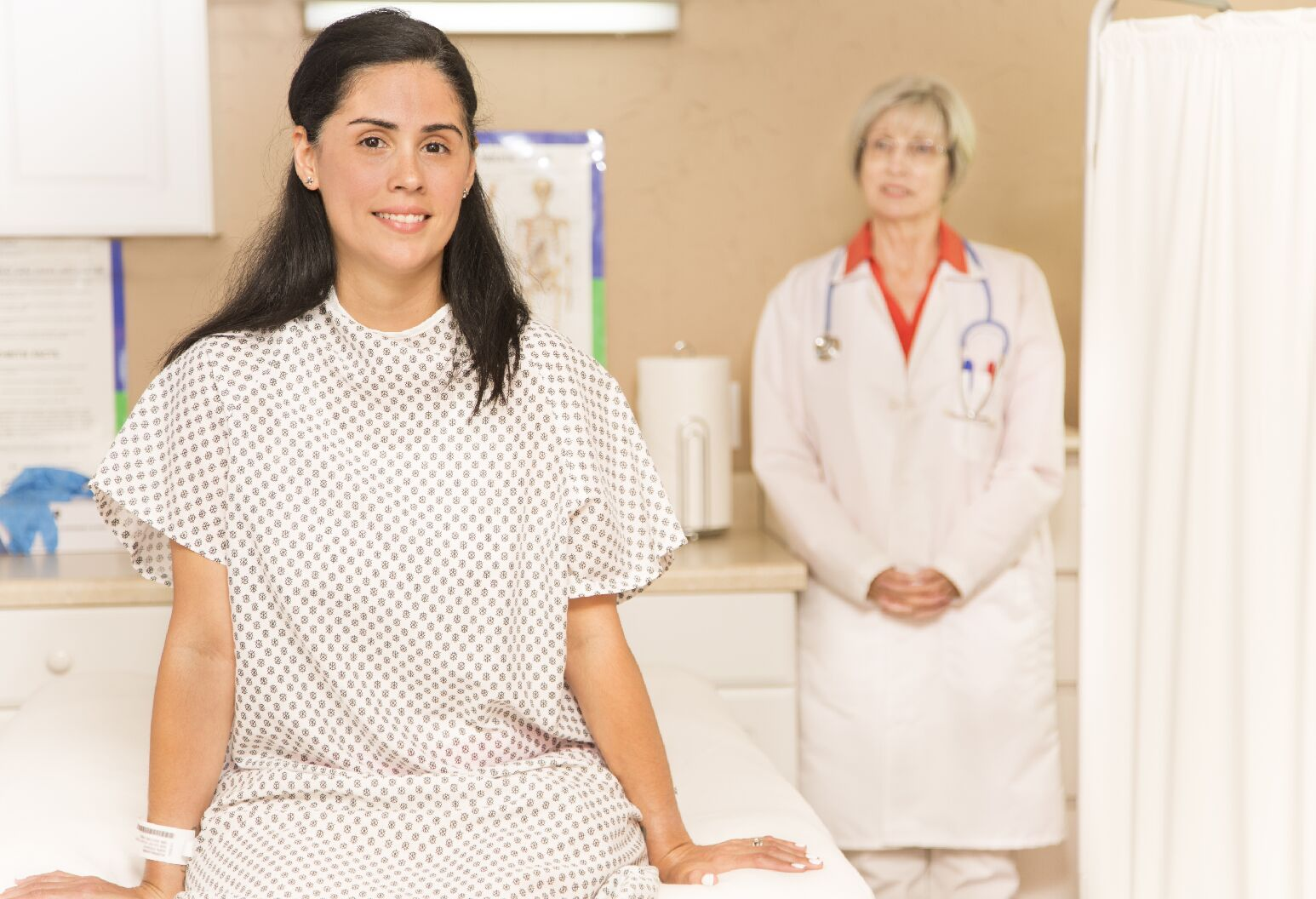 woman in hospital gown sitting on table with doctor in background