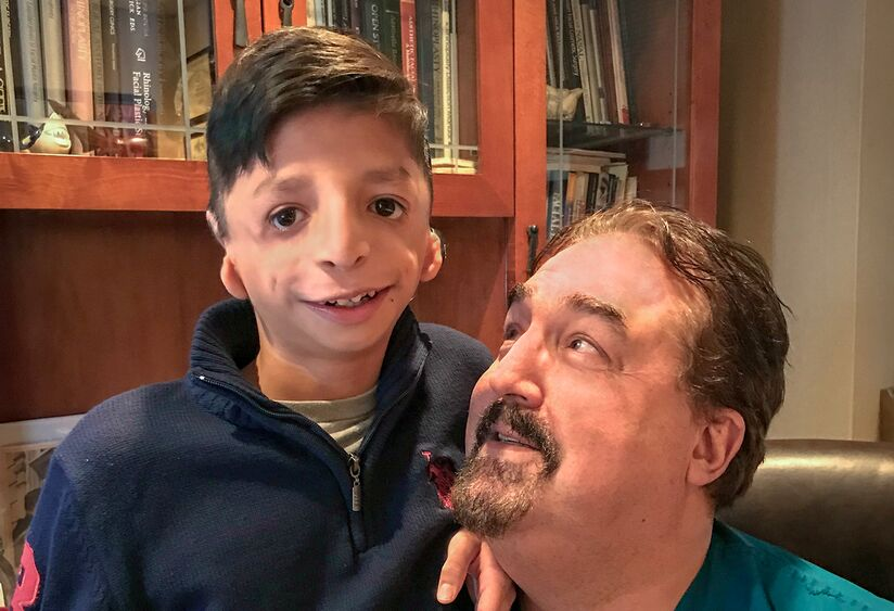 Jared Galicia poses with Thomas Romo, MD, in Romo's office. While Jared smiles at the camera, Dr. Romo looks at him tenderly. Thanks to Dr. Romo's treatment, Jared is starting to feel happier and healthier.