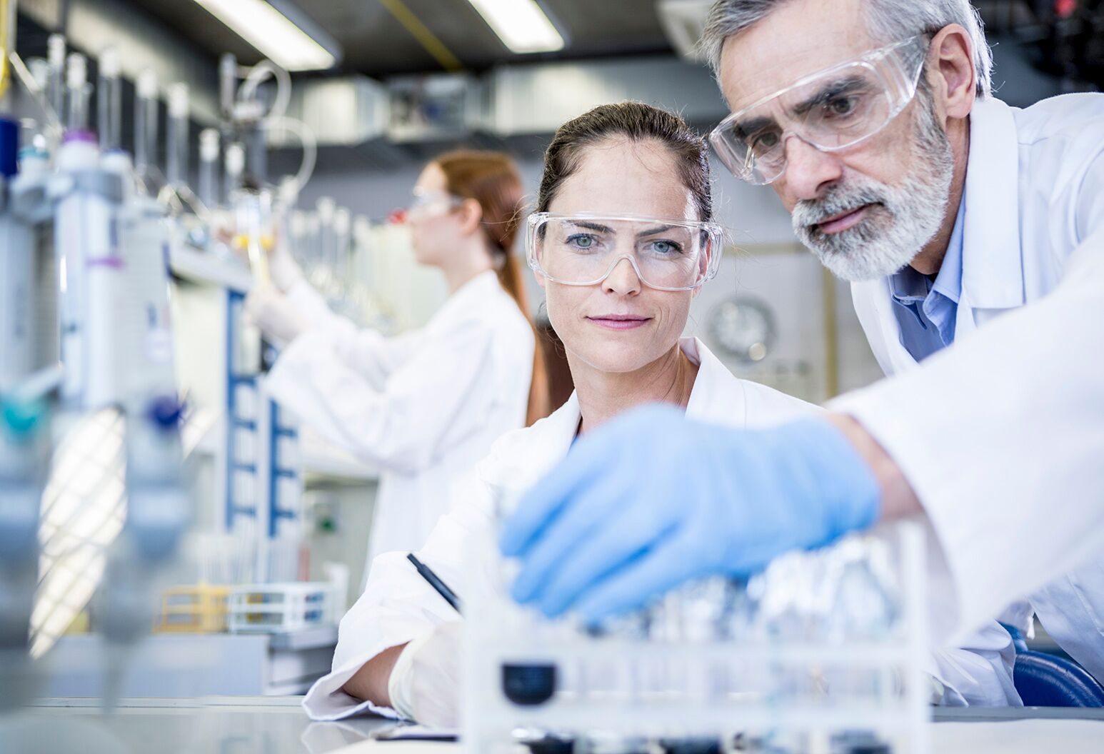 Two scientists with lab coats and safety glasses reviewing a chemical solution.