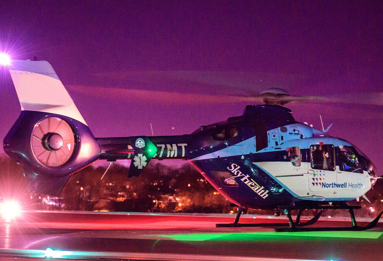 A helicopter sits on a helipad. It is blue and white and says Northwell Health and SkyHealth on the side. The propeller is spinning.