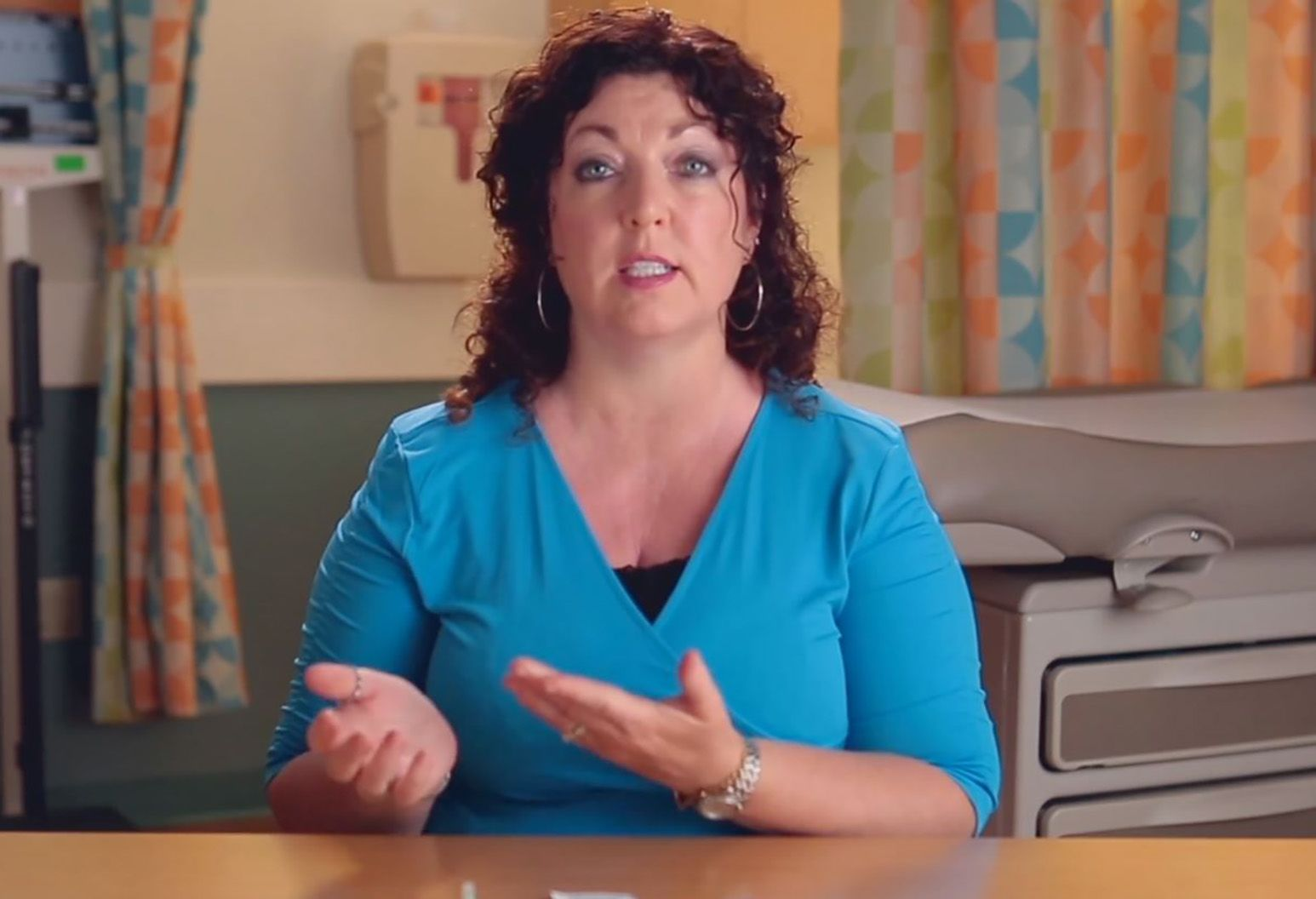A lady with curly brown hair wearing a blue shirt and silver hoops is speaking. She's sitting in a patient room in a hospital.