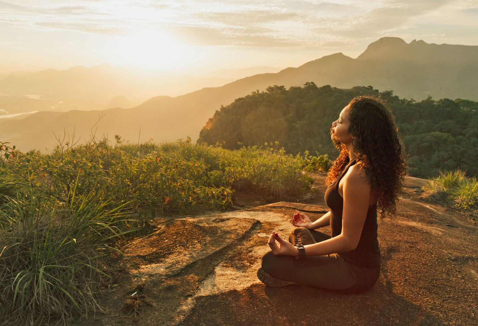 A woman meditates at the top of a mountain.