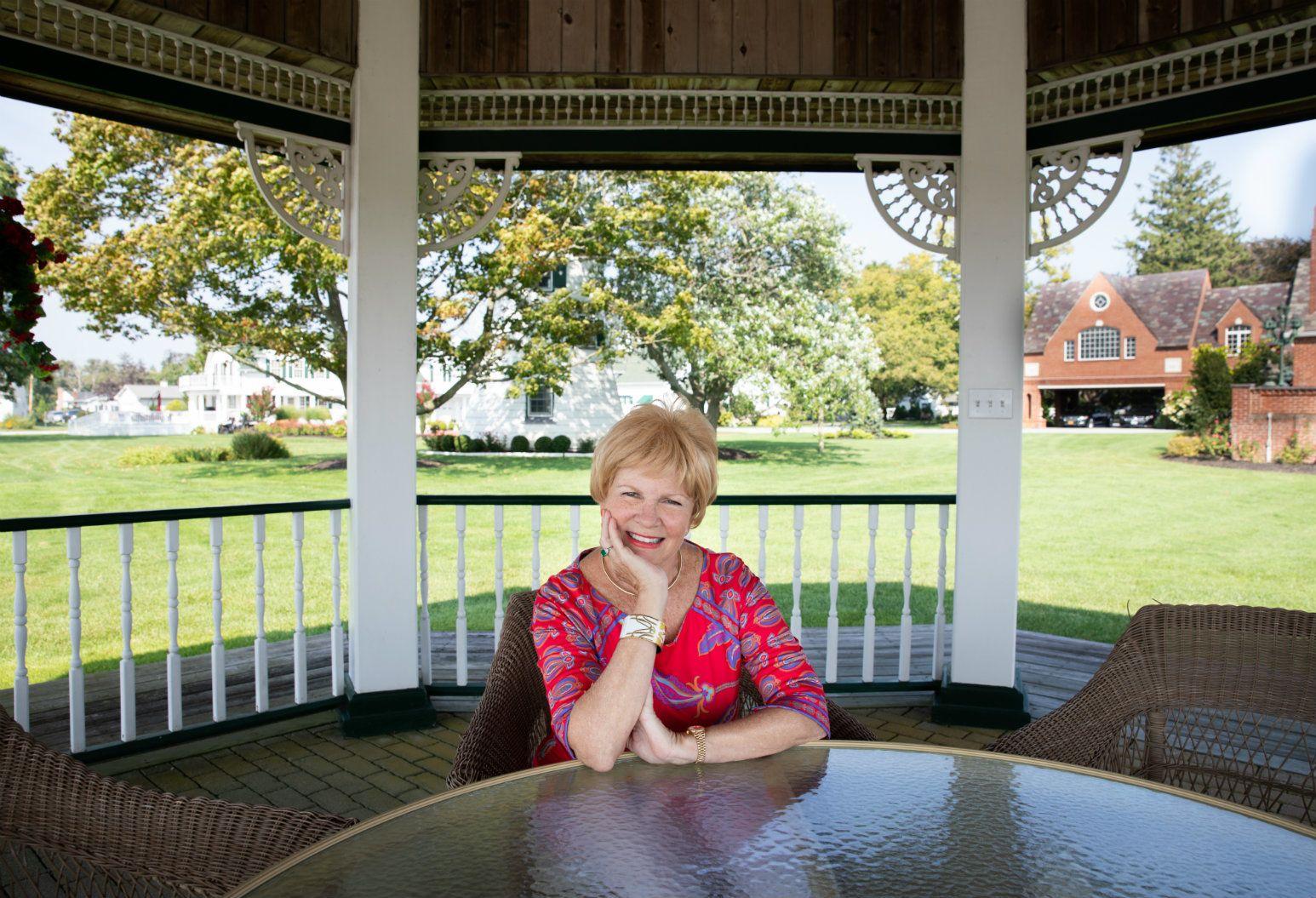 Susan Imbert sits inside a gazebo on a sunny day.