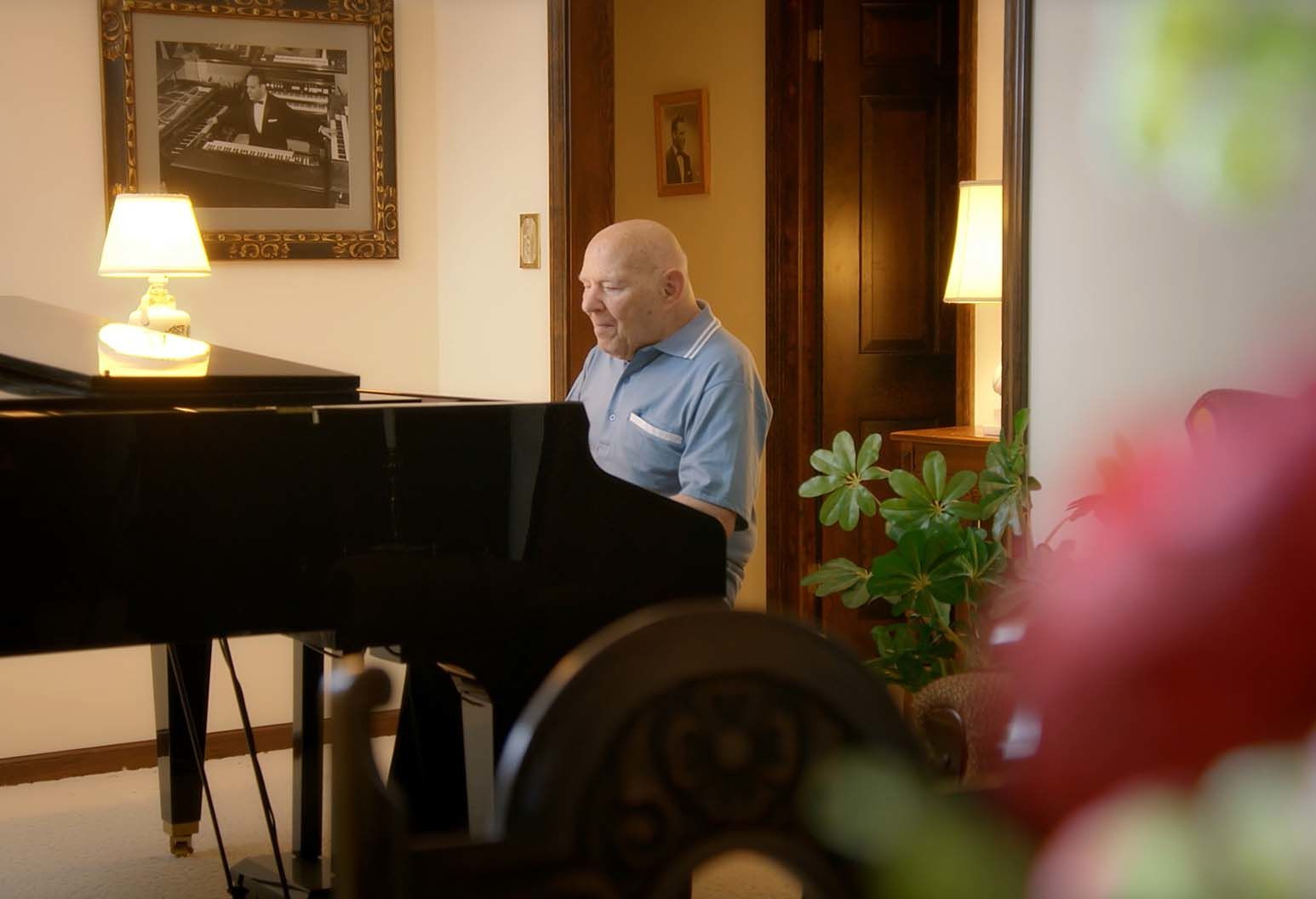 A man wearing a blue shirt plays the piano in the living room of his house.