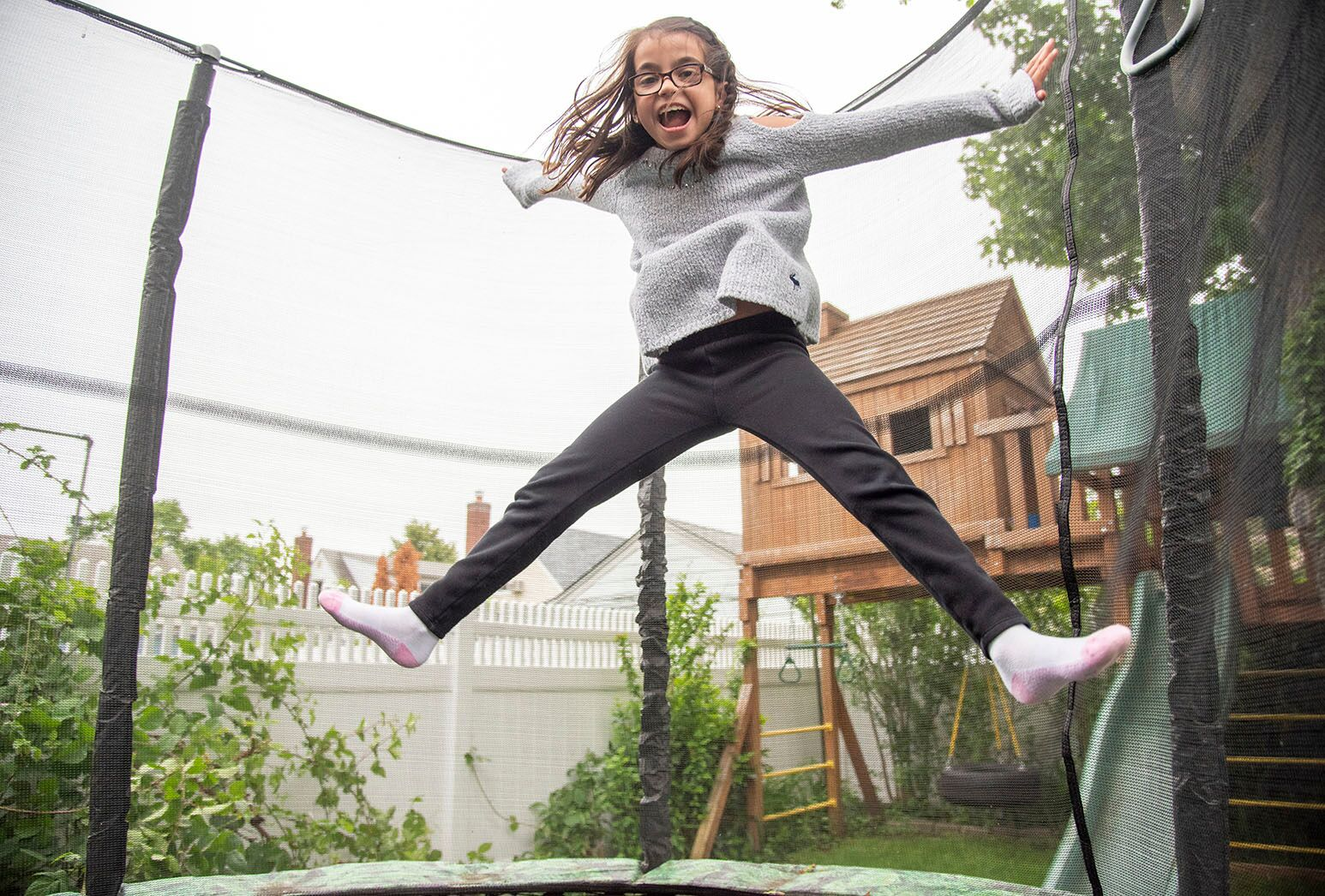 Young girl with brown hair jumps high on a trampoline in her backyard.