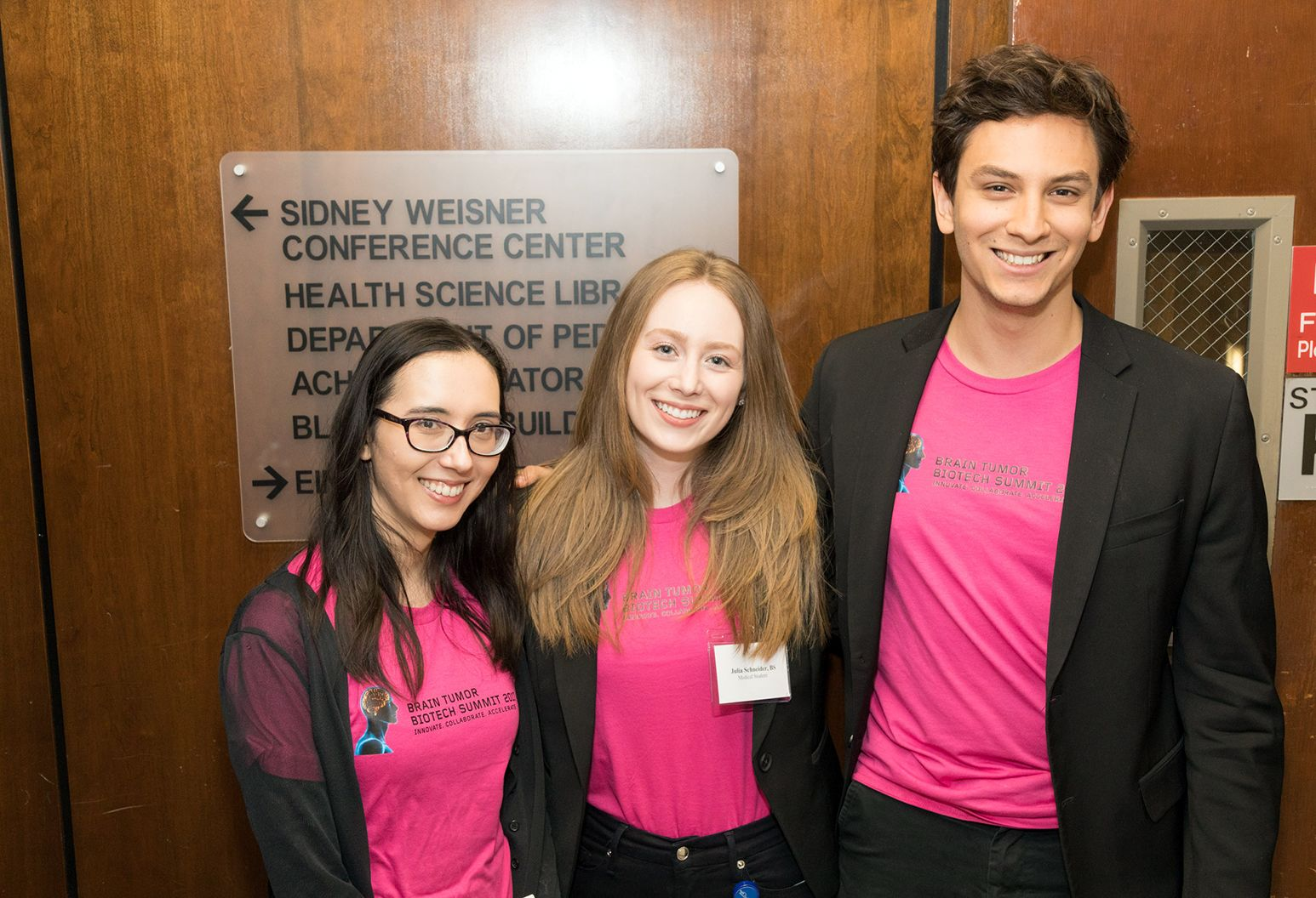 Three young medical students who are wearing matching pink shirt pose for a group photograph