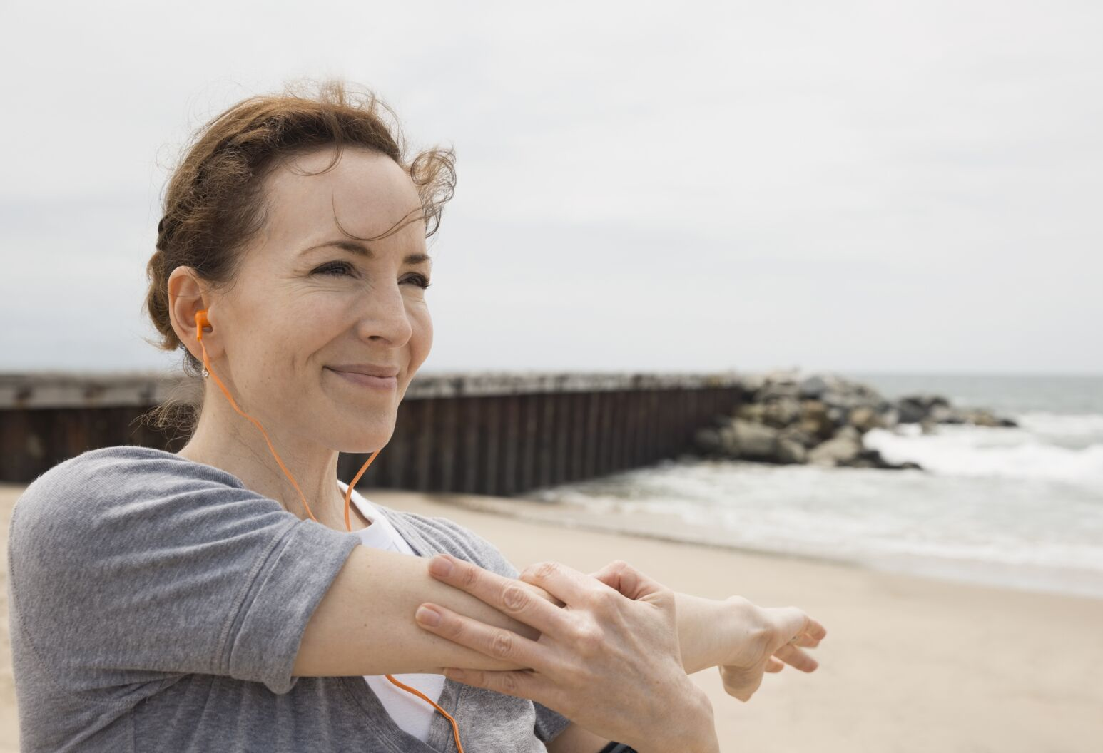 Woman stretching her arm while on a run on a beach