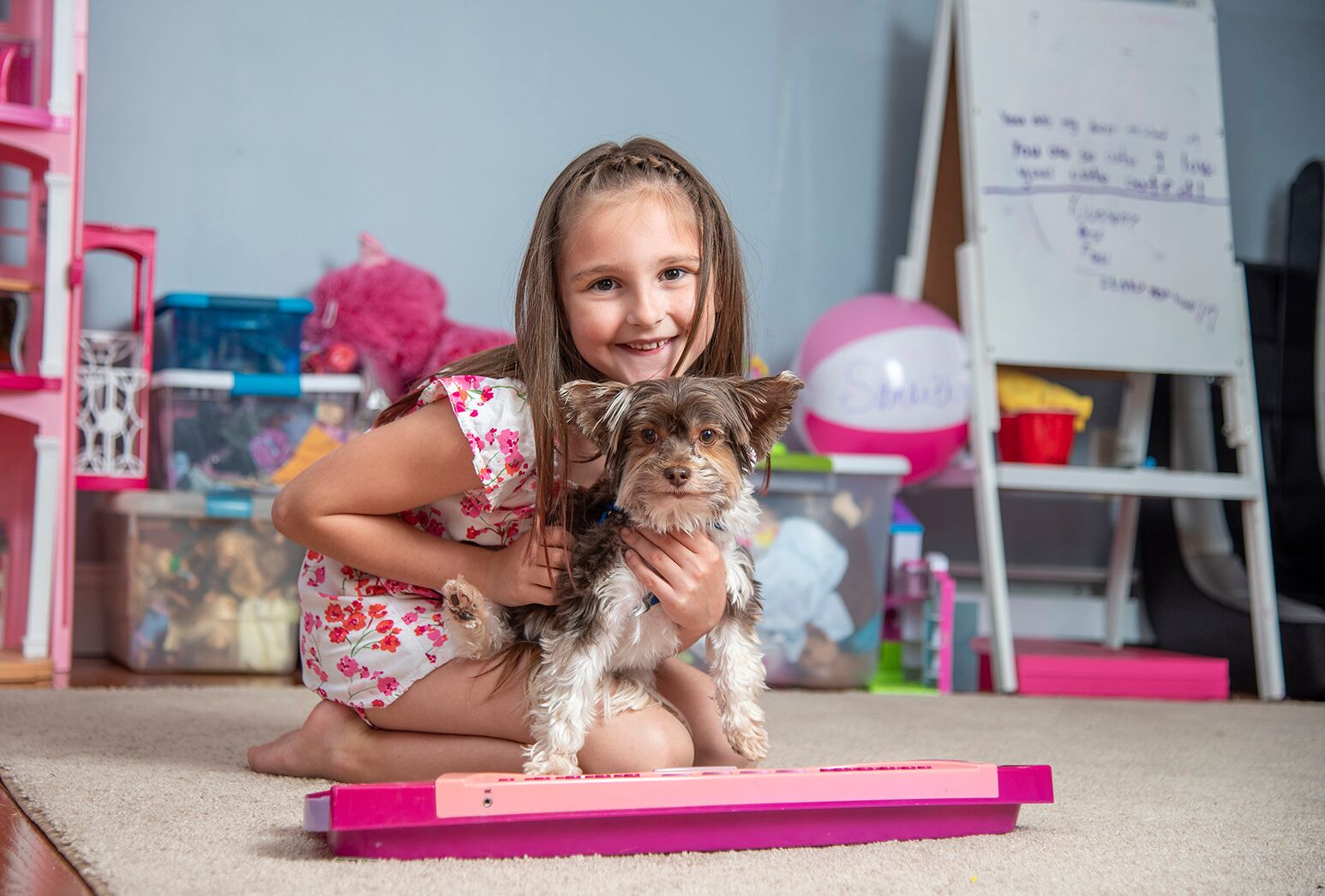 Young girl with long brown hair in a pink and white romper, with her little dog.