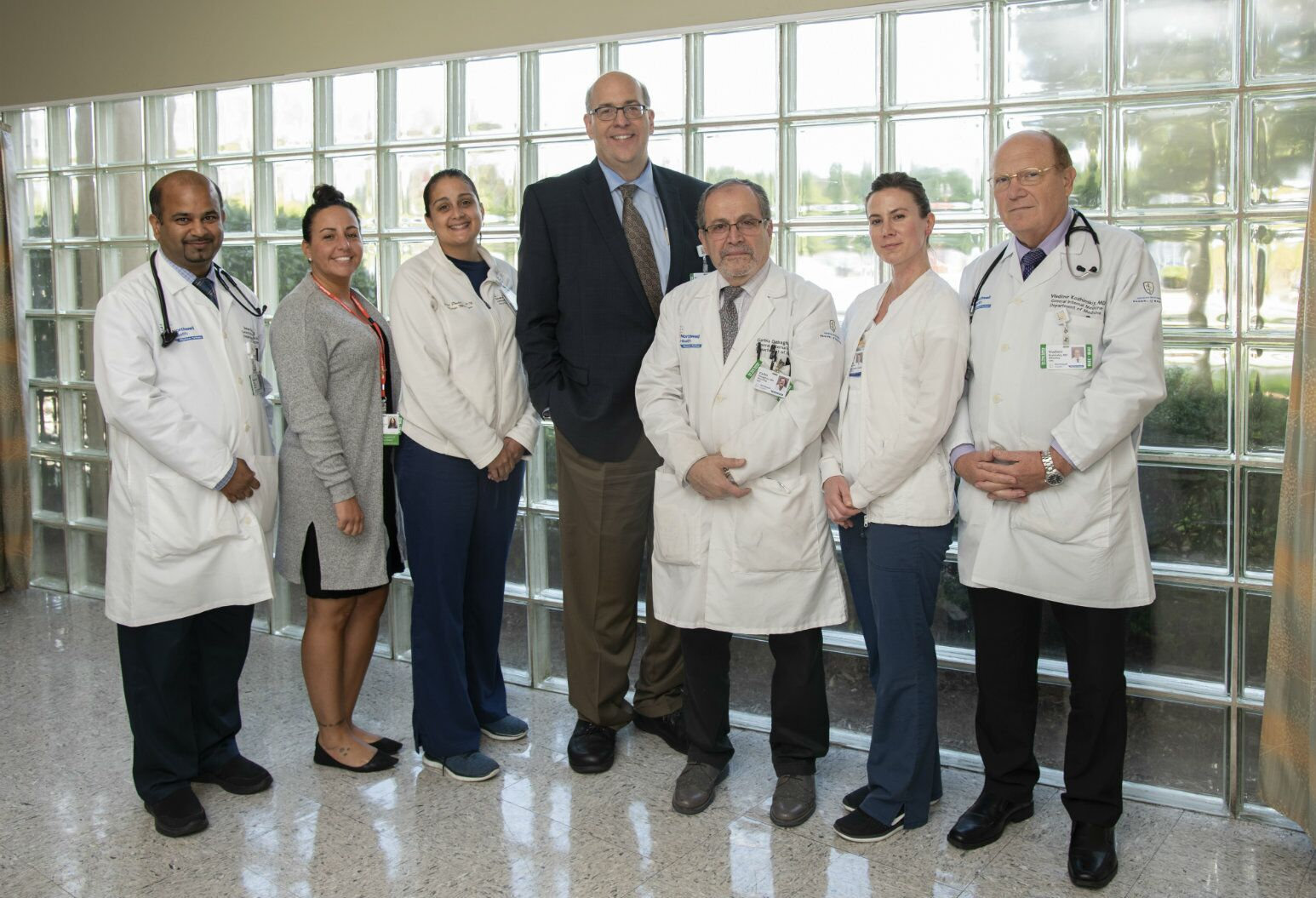 Matthew Weeks, MD, and other doctors and administrators pose for a picture in front of an opaque glass wall.