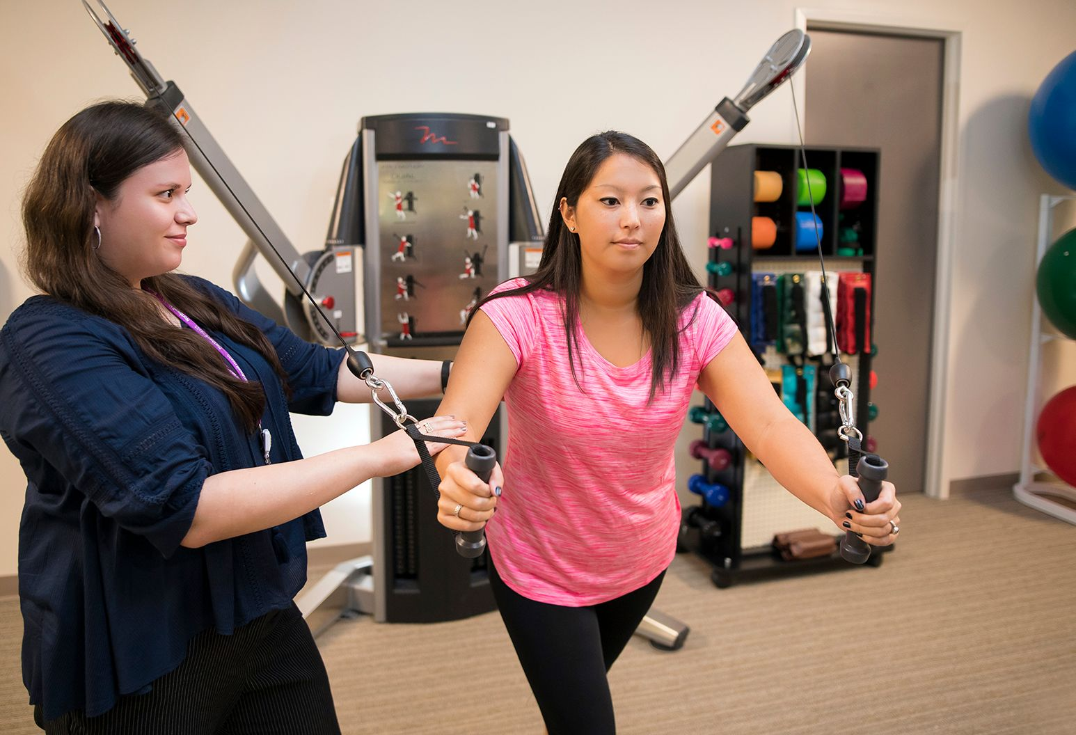A young woman being examined by a female physical therapist. She is testing her arm strength.